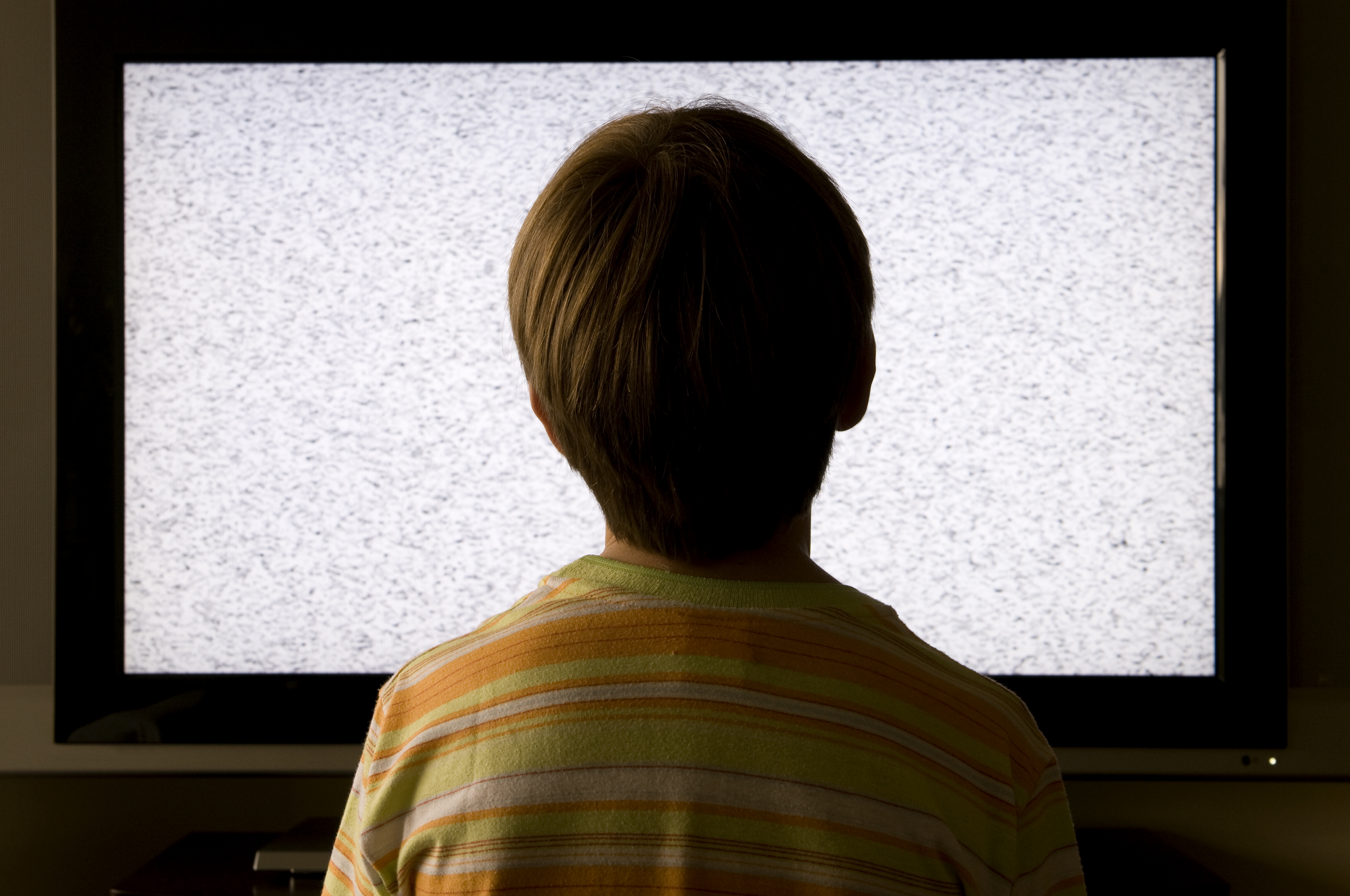 Boy in front of a broken TV playing static