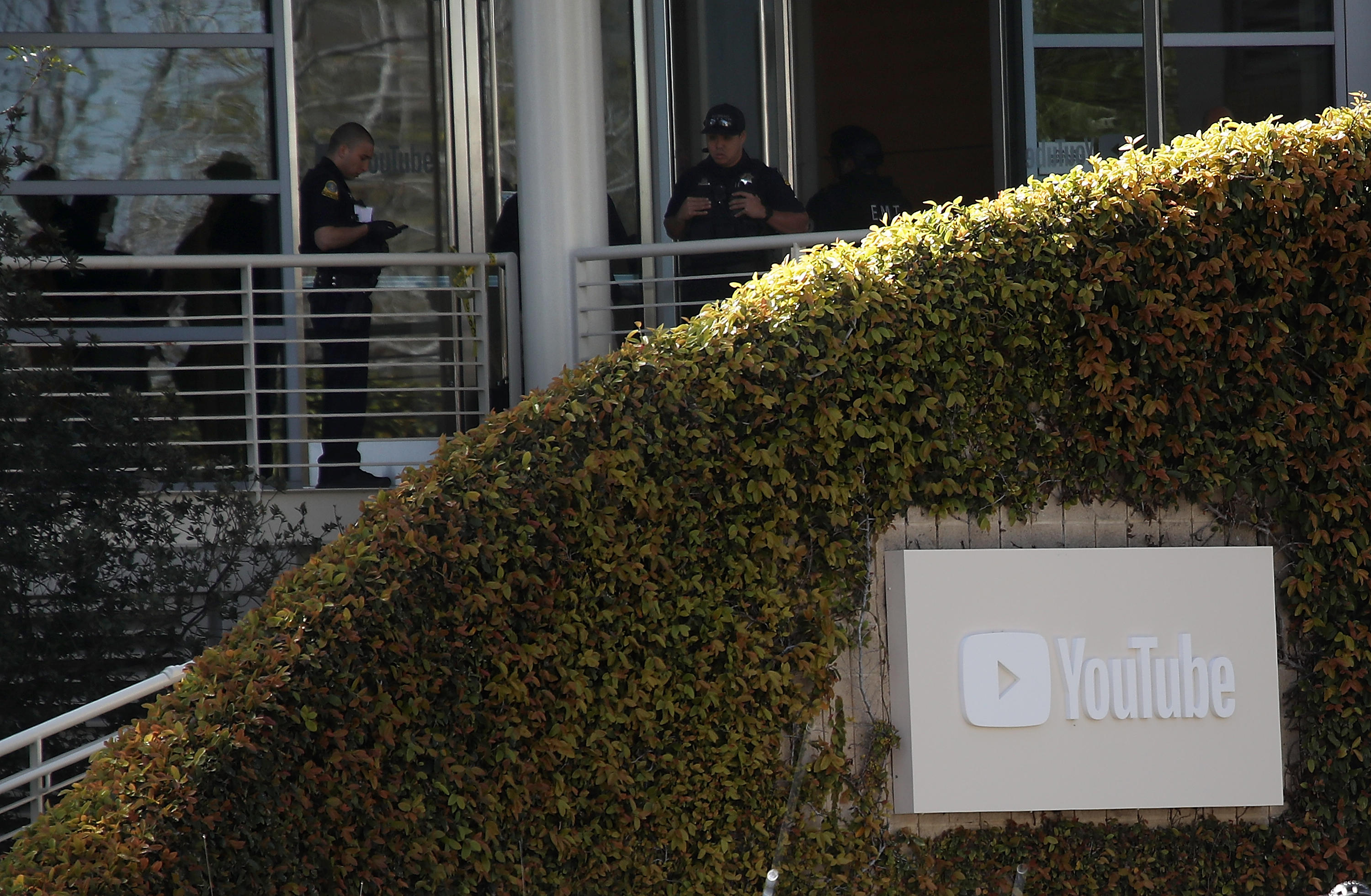 Police officers stand on a balcony behind a large bush that surrounds a YouTube sign