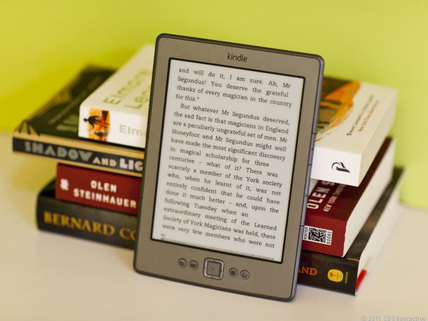 A Kindle e-reader leaning on a stack of books.