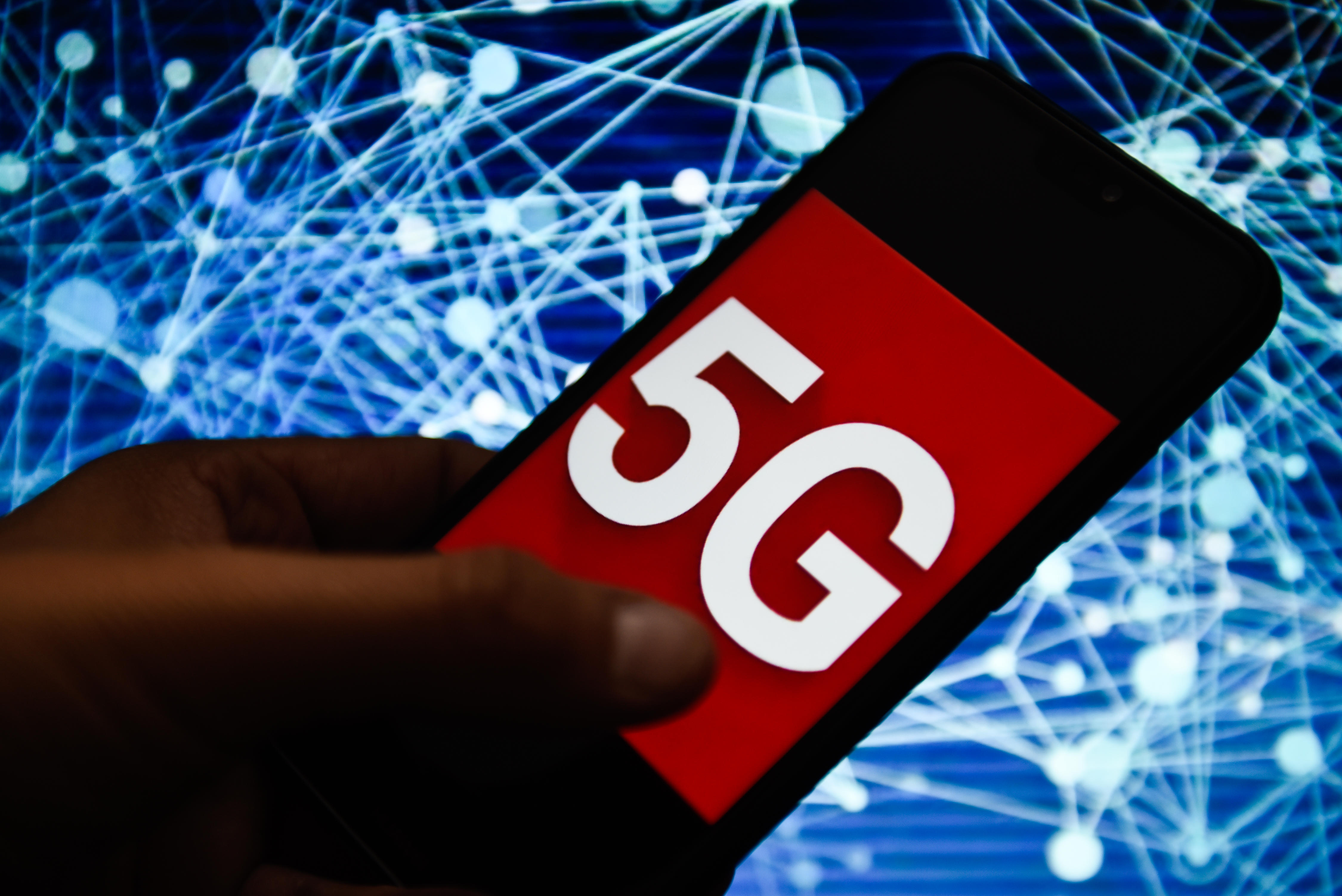 In this photo illustration a 5G logo seen displayed on a