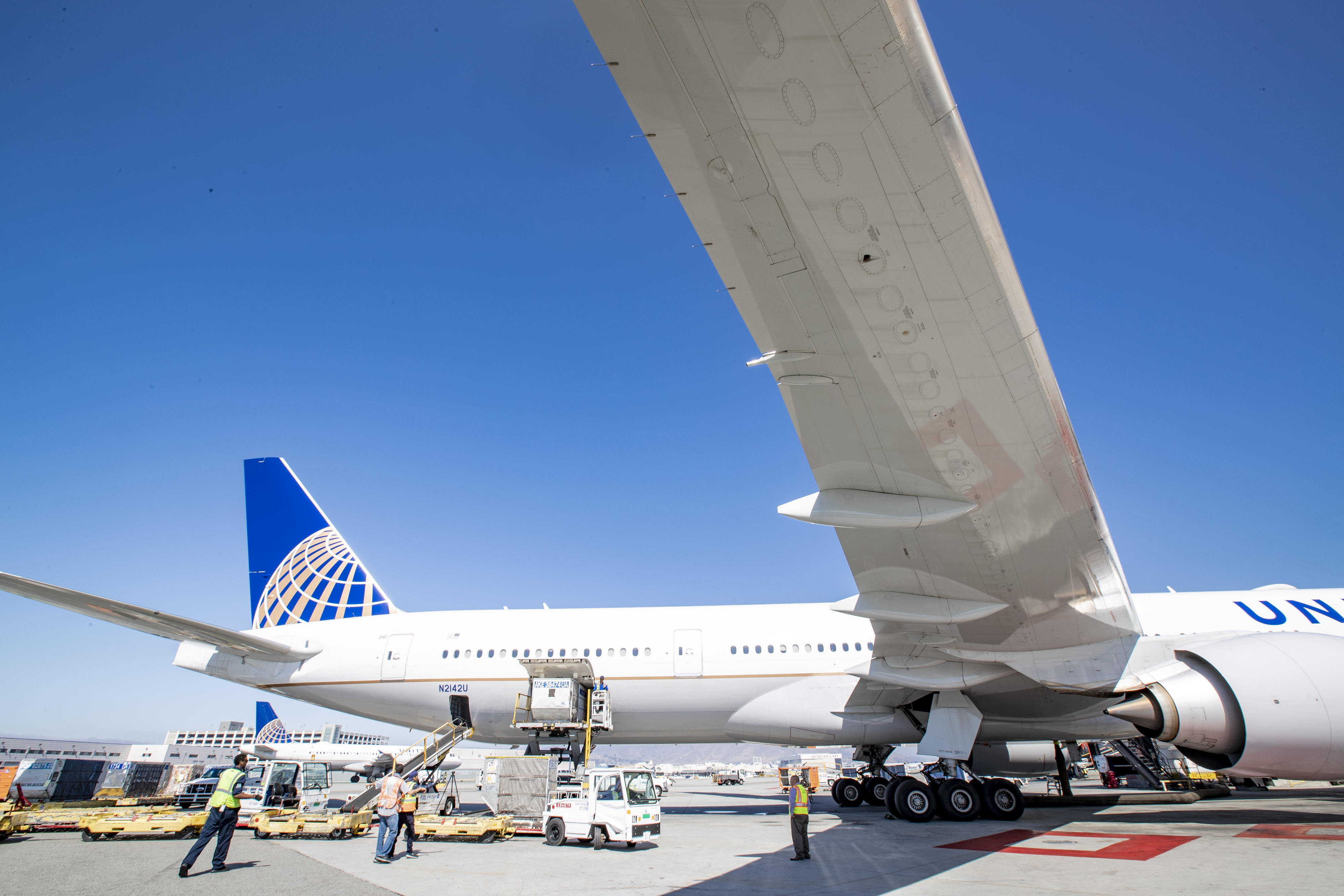 Activity around a United Airlines aircraft during servicing.