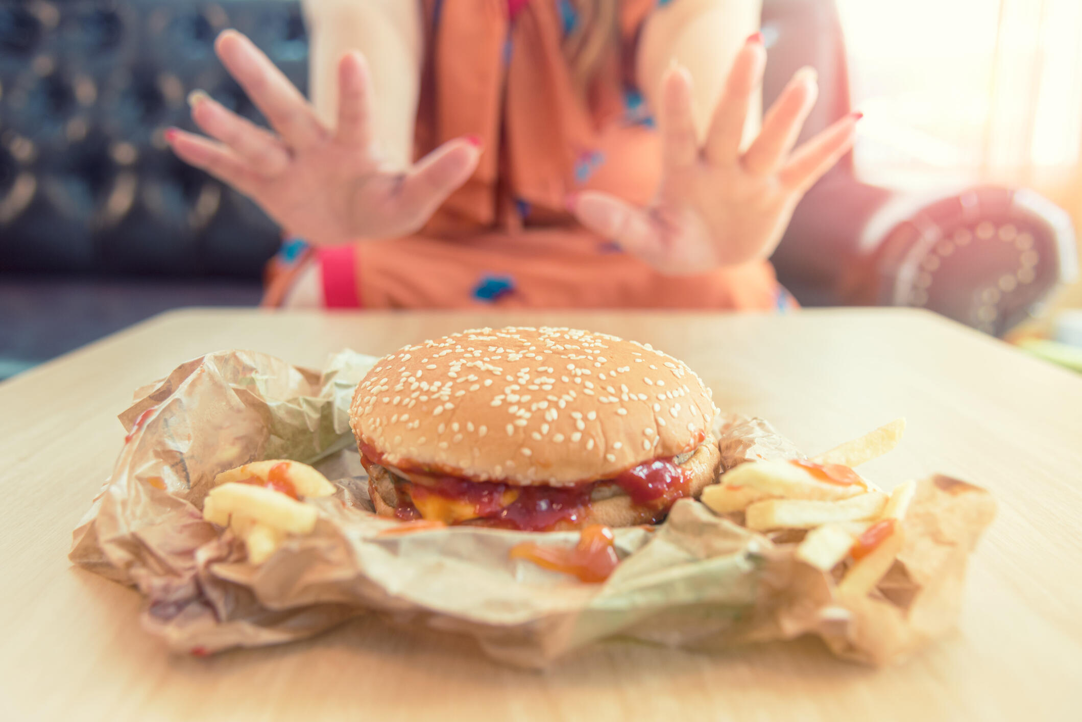 close up of hands woman refusing a cheeseburger on a diet