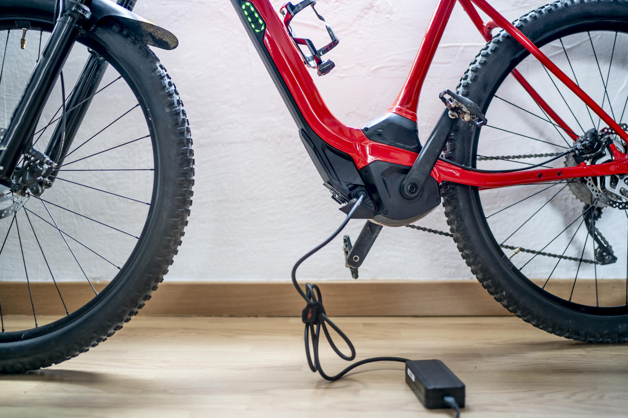 Close-up of the frame of a red e-bike connected to a charger