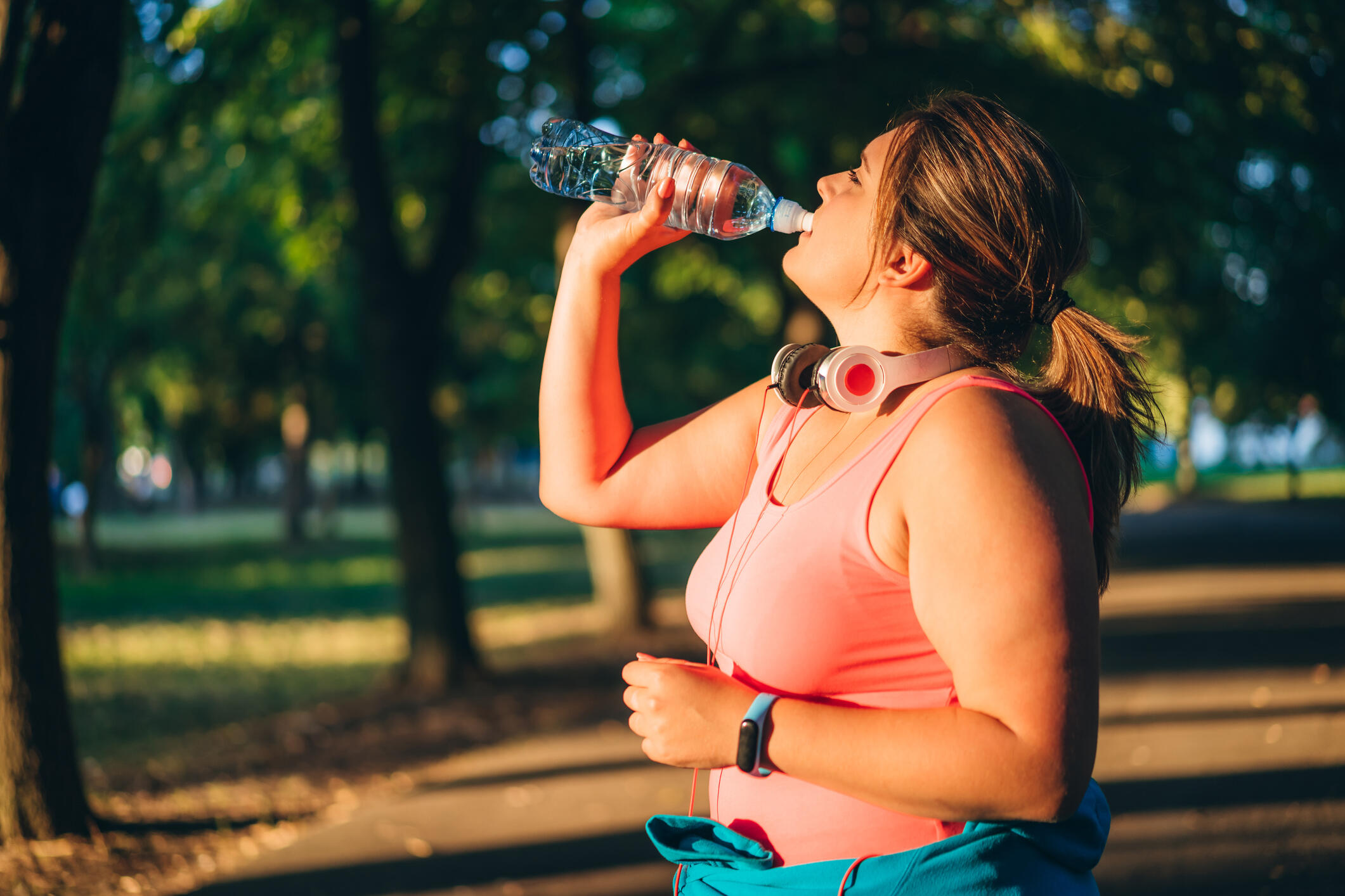 Young woman dressed in workout clothes standing a park, drinking from a plastic water bottle