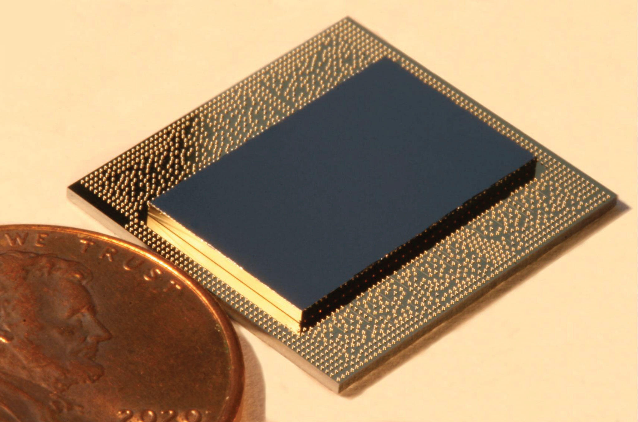 IBM's Falcon quantum computing chip is shown next to a penny.