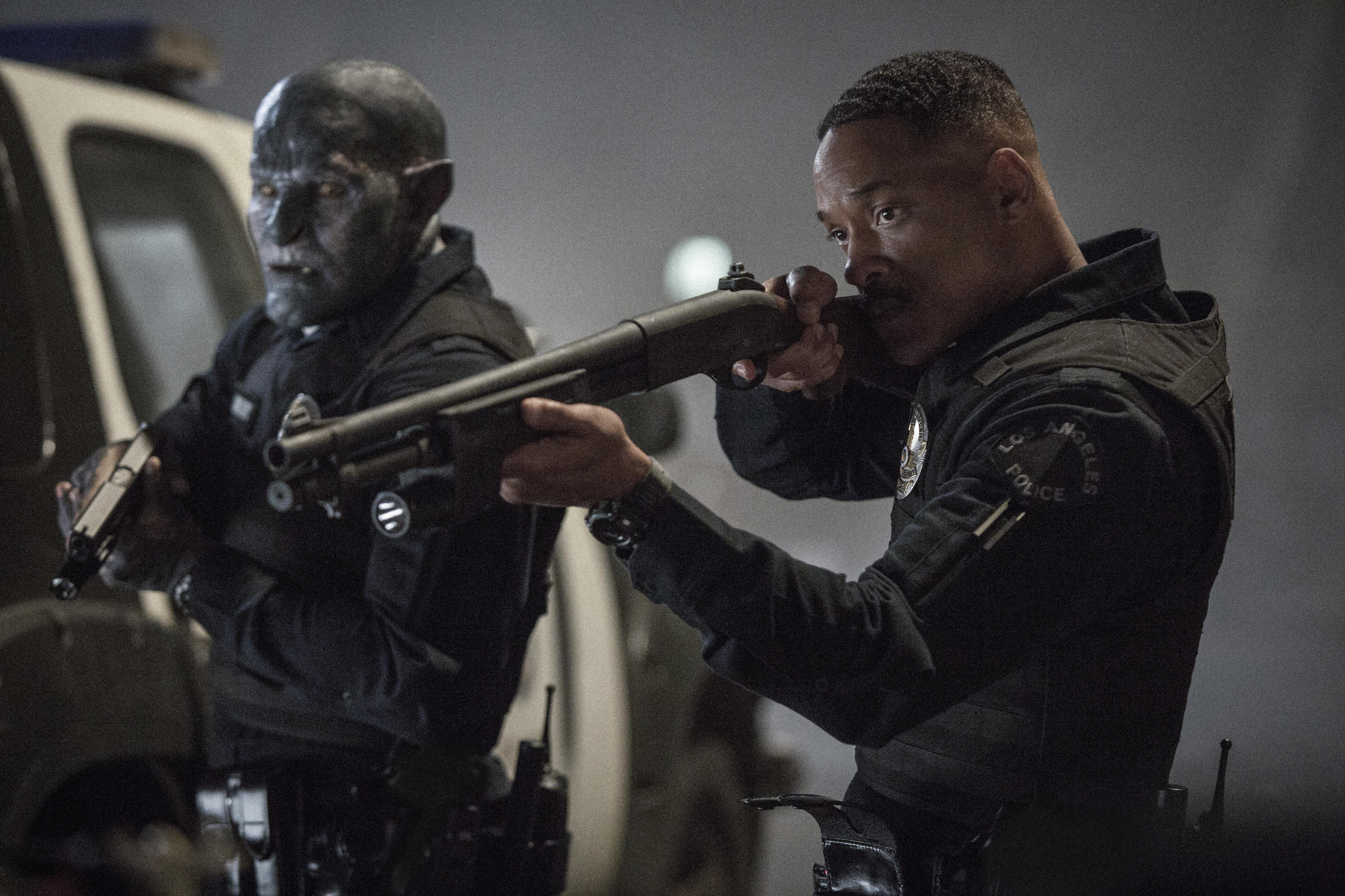 """Will Smith, playing Ward in """"Bright,"""" holds a gun next to his orc partner"""