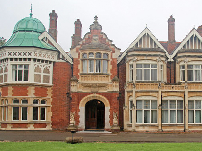 A photograph of Bletchley Park, a mansion with large grounds purchased by the British Government to house its codebreaking operation during WWII. The house is made mostly of red brick and combines several architectural styles.