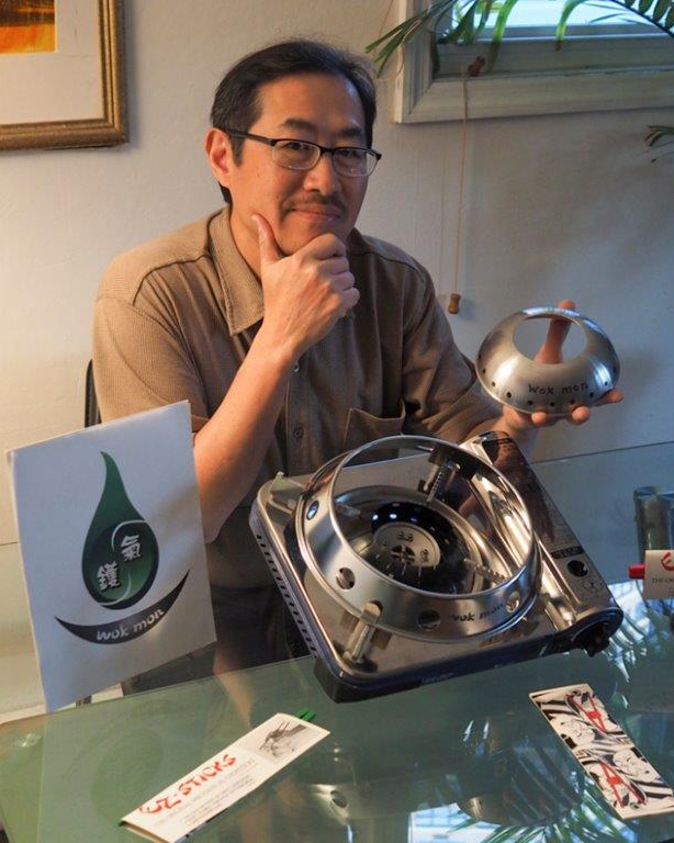 Glen Lee, the inventor of the WokMon poses with his invention and a portable burner. The secret is a focusing ring that concentrates flames from a gas range into one area.