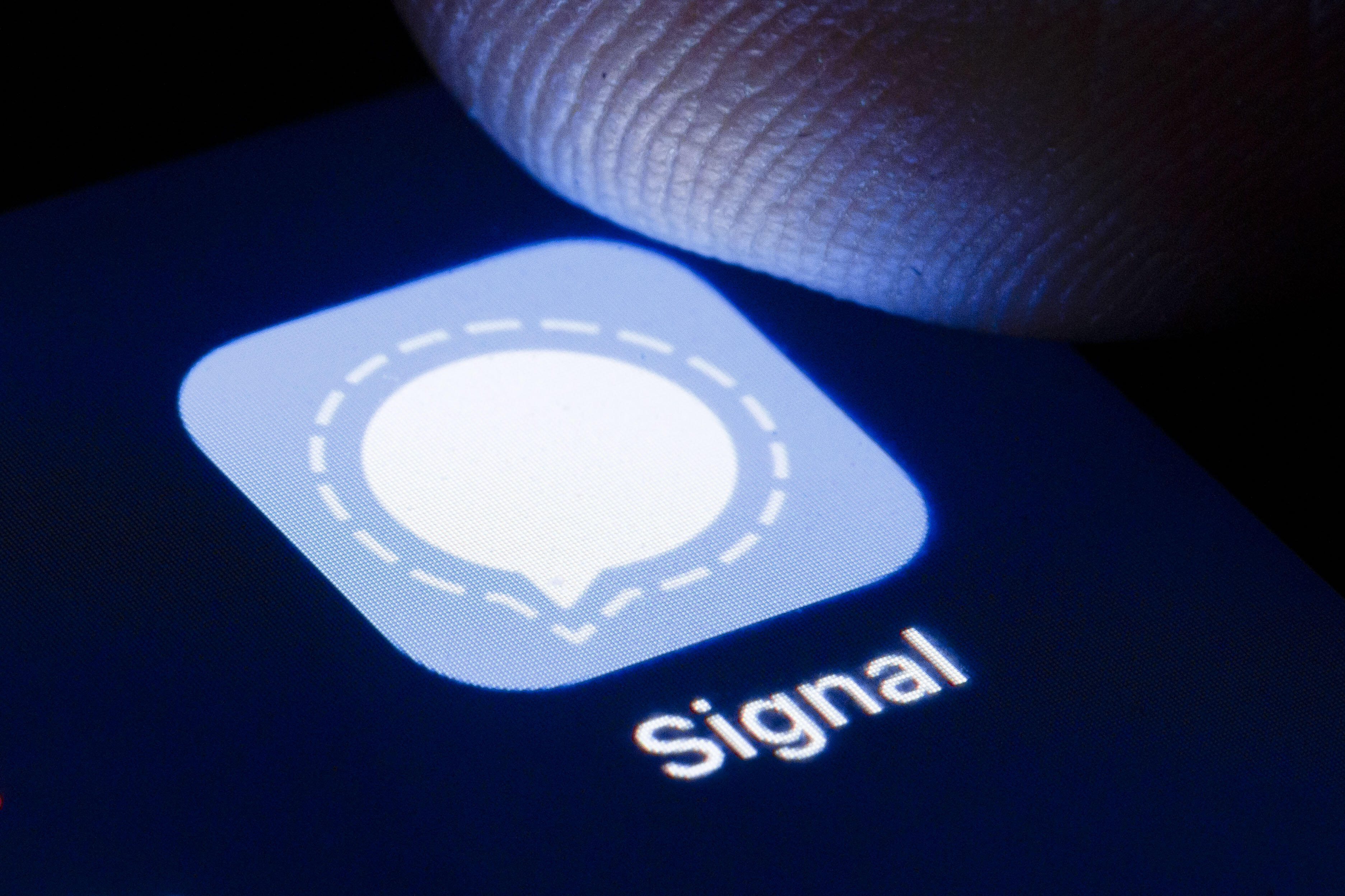 A finger hovers over a phone screen where the icon for the Signal encrypted messenger app is displayed.