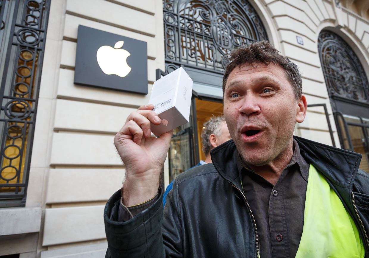 Mikhail Vorobyev, one of the early customers to buy an iPhone 5 at Apple's store in Paris, shows off his new purchase.