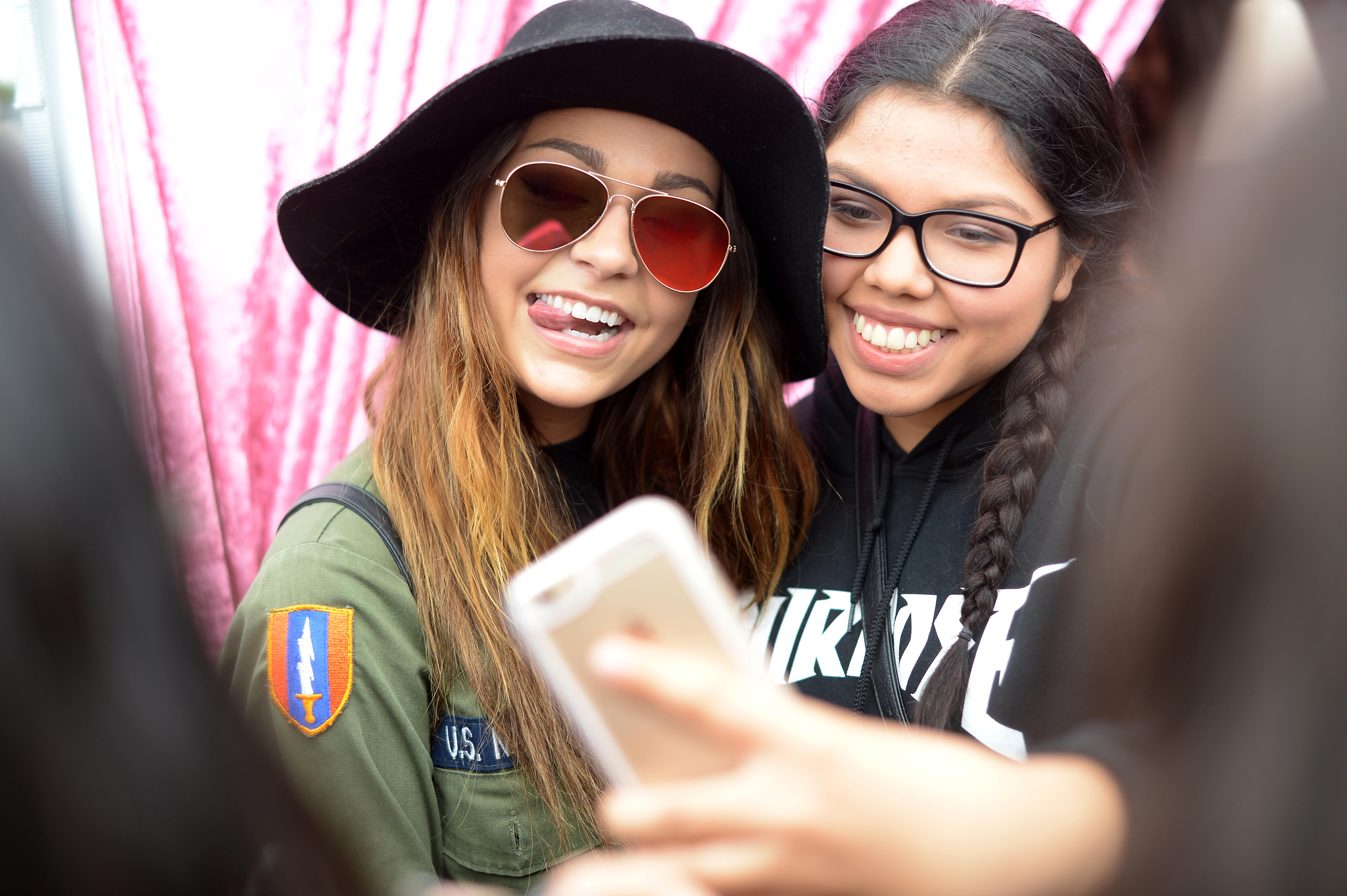 YouTuber Andrea Russett poses while a fan shoots a selfie