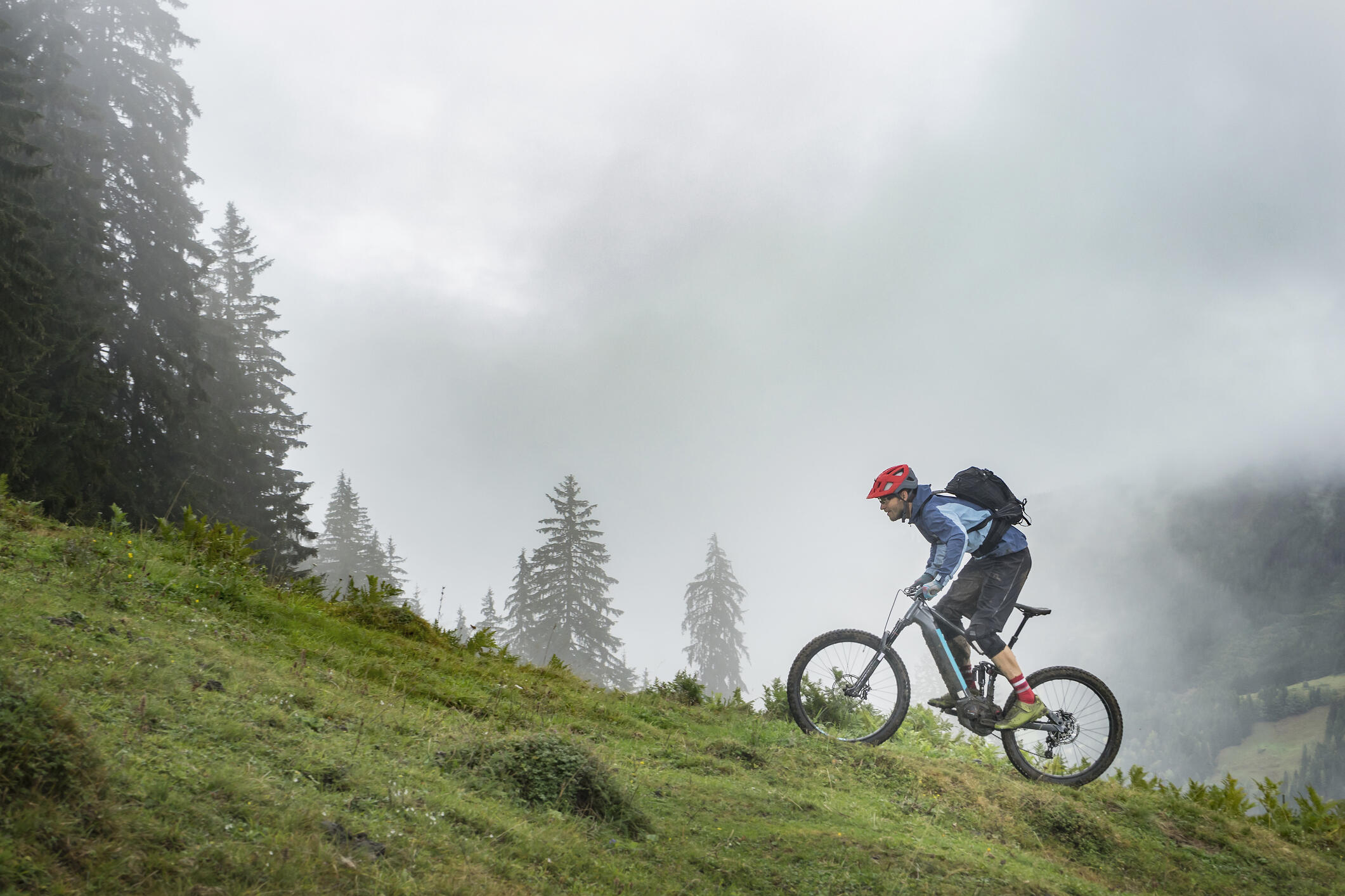 A man rides and e-bike up an incline on a mountain biking trail