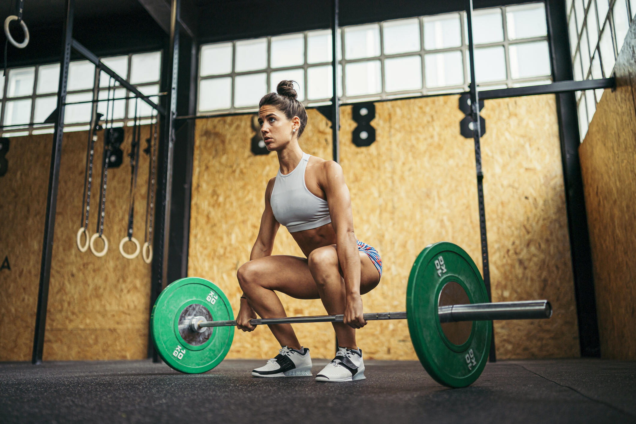 A young woman preparing to perform a deadlift in a gym.