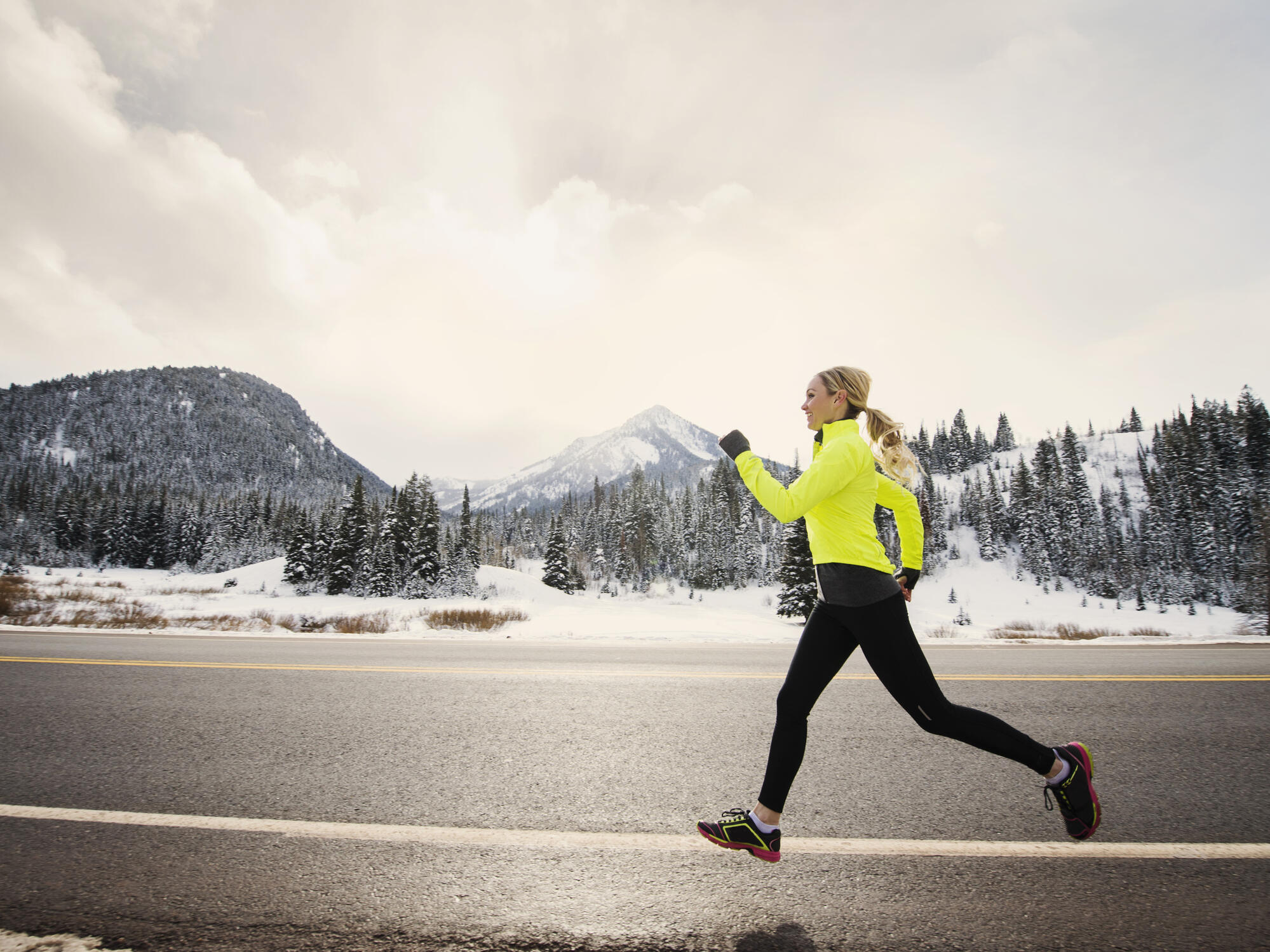 Blonde-haired woman in a neon jacket running outdoors in snowy weather.