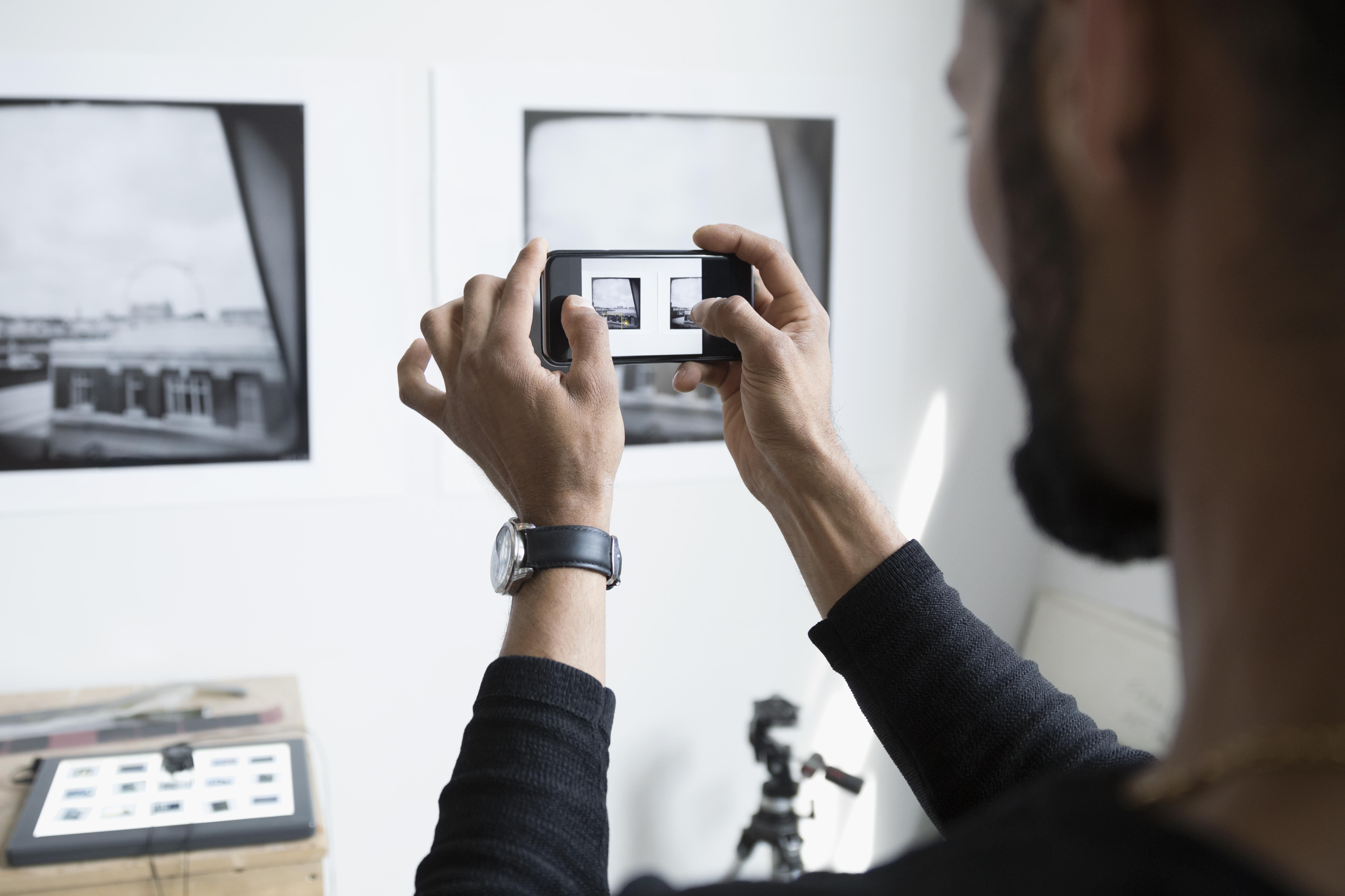 Male photographer with camera phone photographing prints on wall in art studio