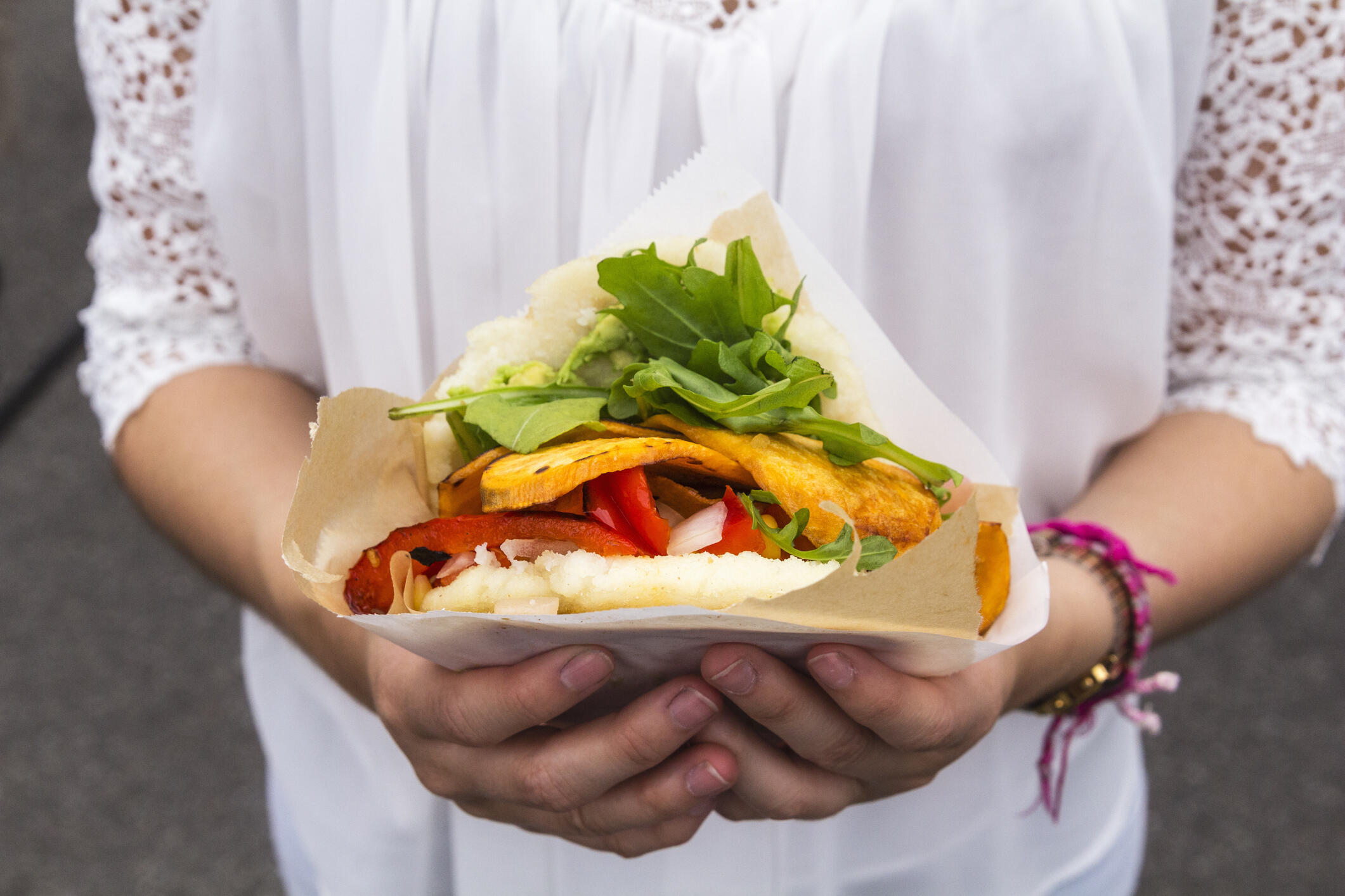 woman in white shirt holding vegan sandwich, close-up of hands