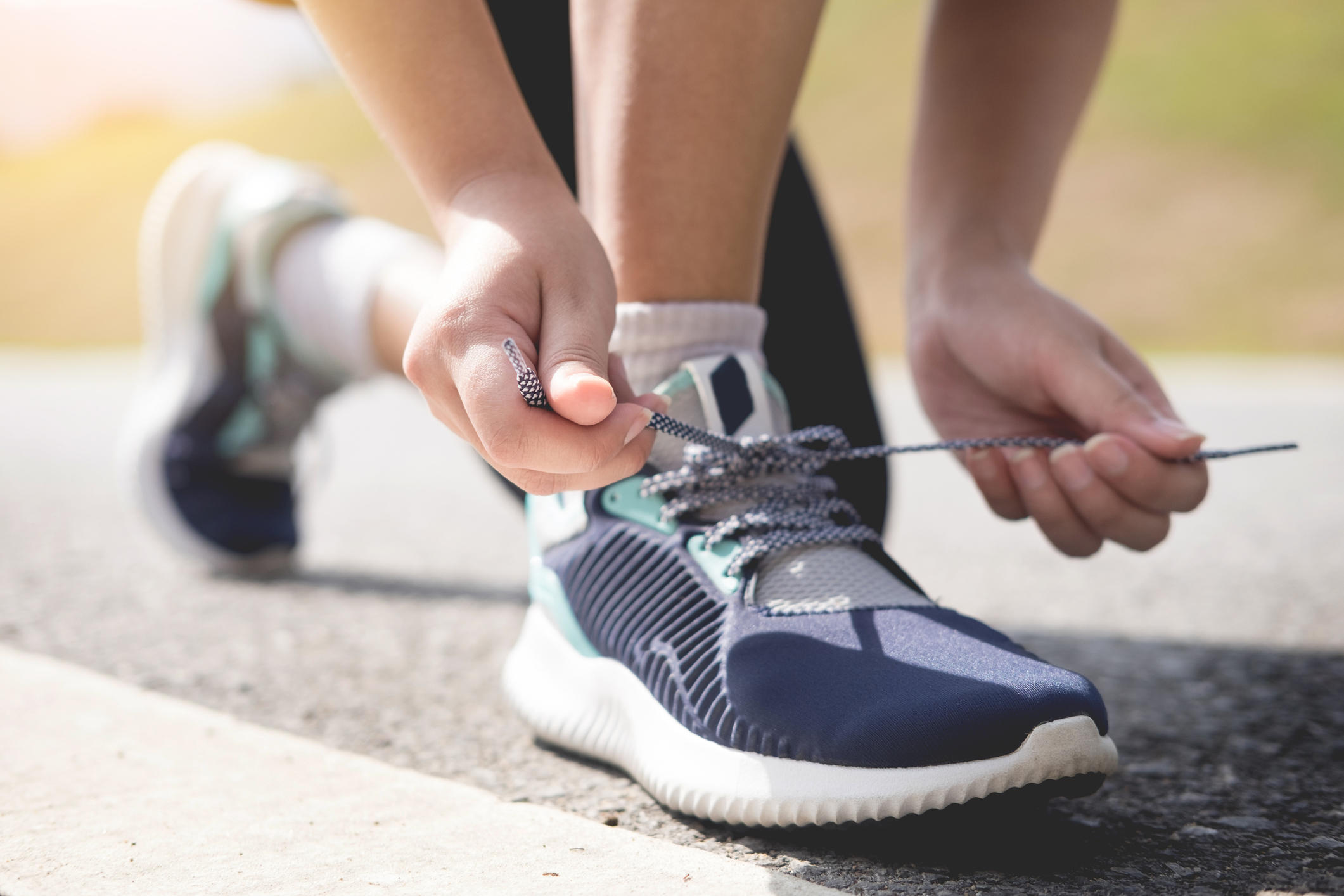 Low Section Of Woman Tying Shoelace On Road