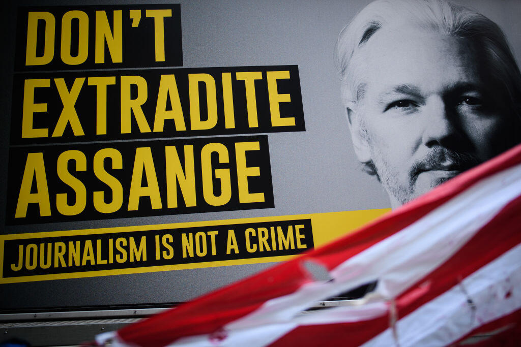 """Sign with a photo of Julian Assange and a message reading """"Don't extradite Assange. Journalism is not a crime."""""""