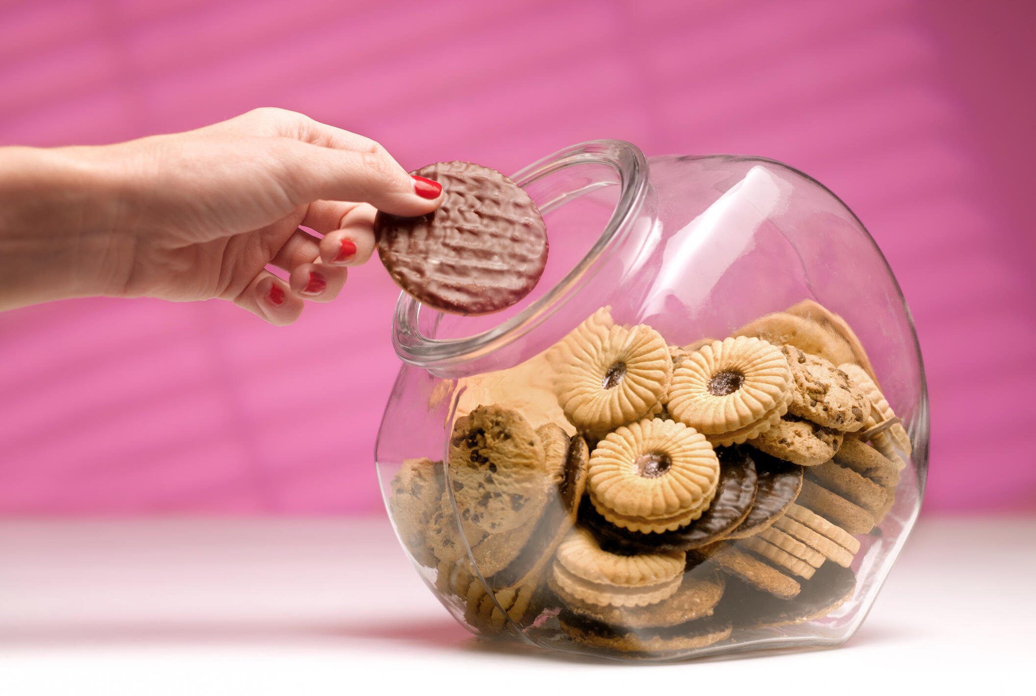 hand taking a cookie out of a cookie jar, pink background