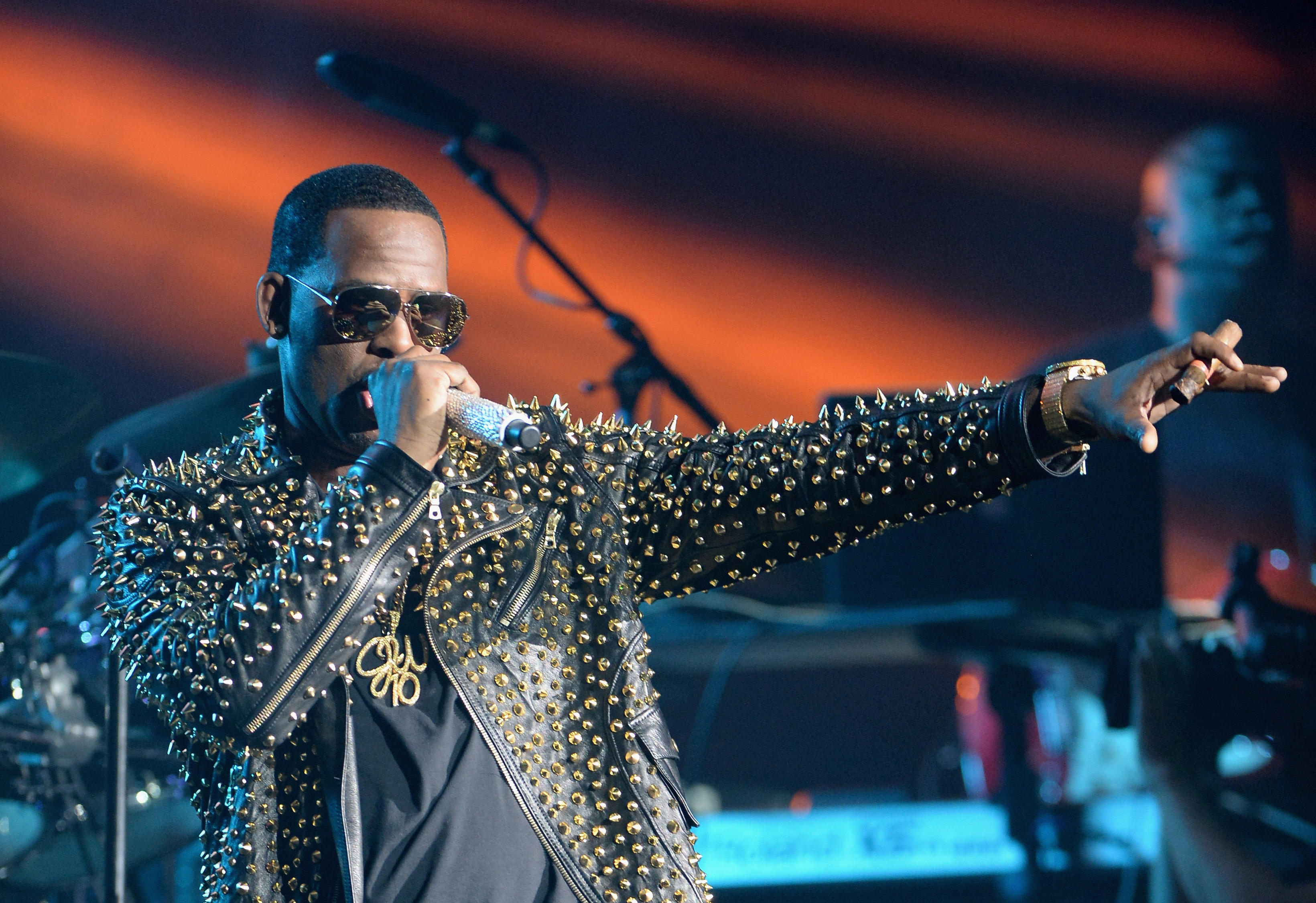 R. Kelly sings into a microphone in a studded leather jacket
