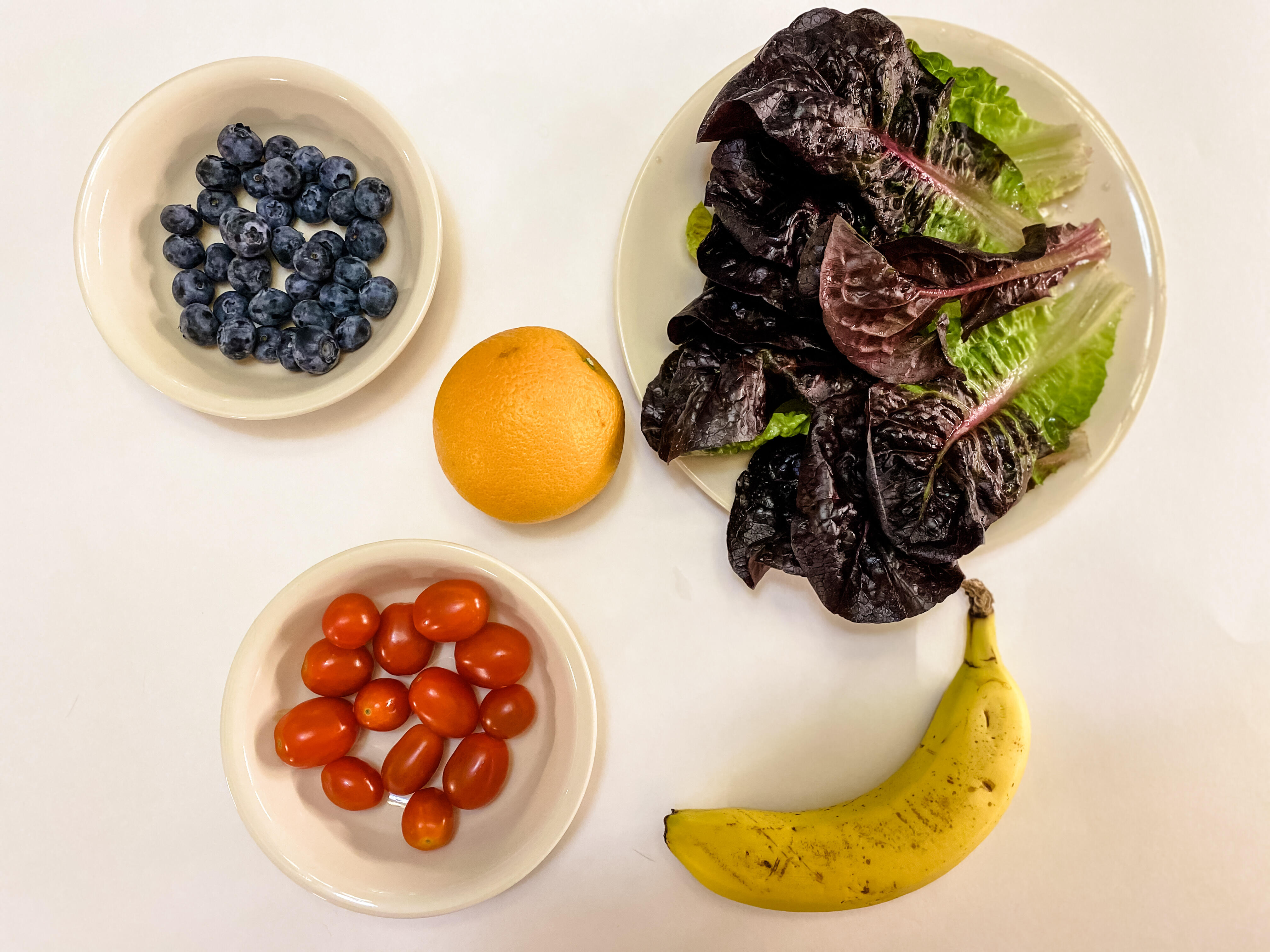 Five servings of produce: one cup of lettuce, one medium banana, one orange, a half cup of cherry tomatoes, and a half cup of blueberries