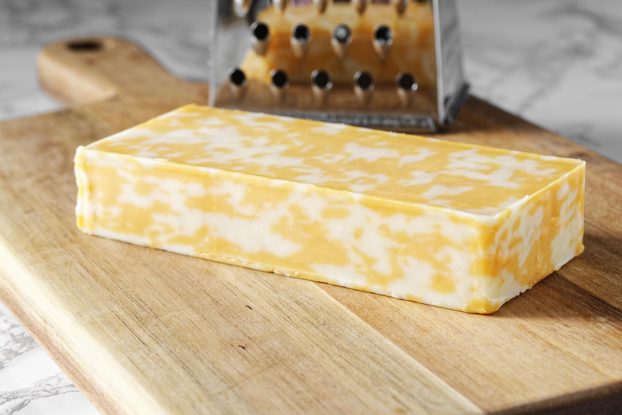 a block of cheddar jack cheese sits next to a cheese grater