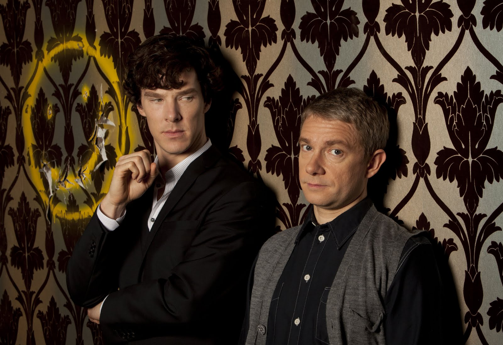 The wallpaper and yellow spray-painted happy face decorate the flat that Sherlock and Dr. Watson share.