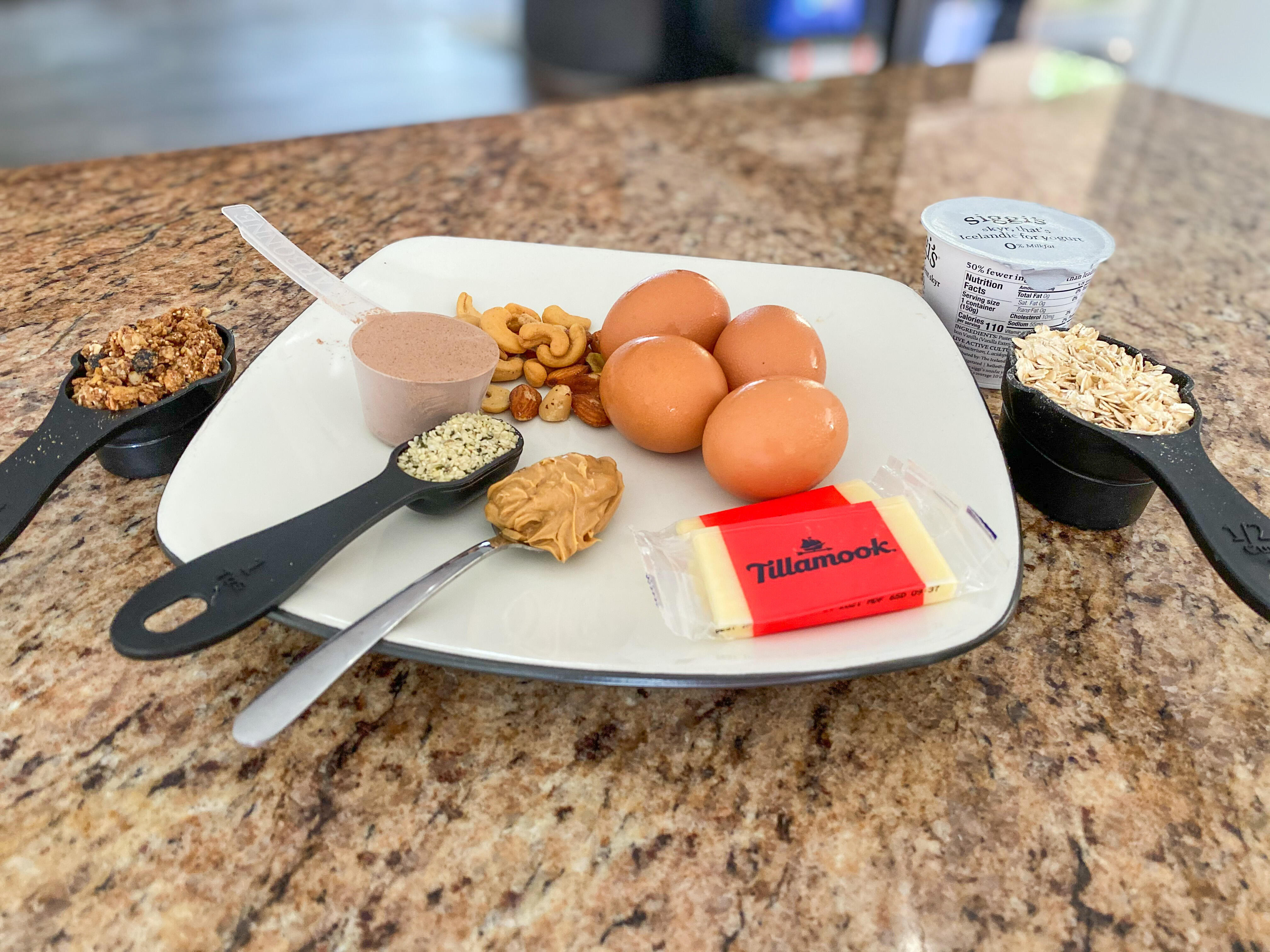 a spread of food containing granola, protein powder, hemp seeds, peanut butter, cheese, nuts, eggs, oats, and yogurt depicting 100 grams of protein