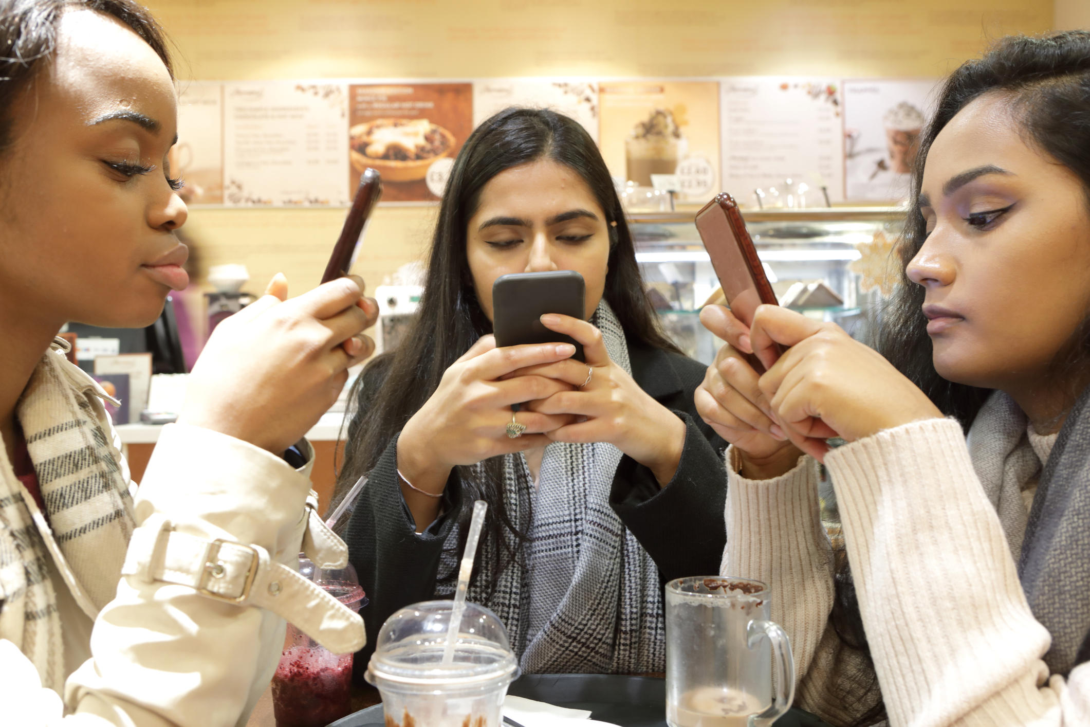 Three young woman on phones in cafe