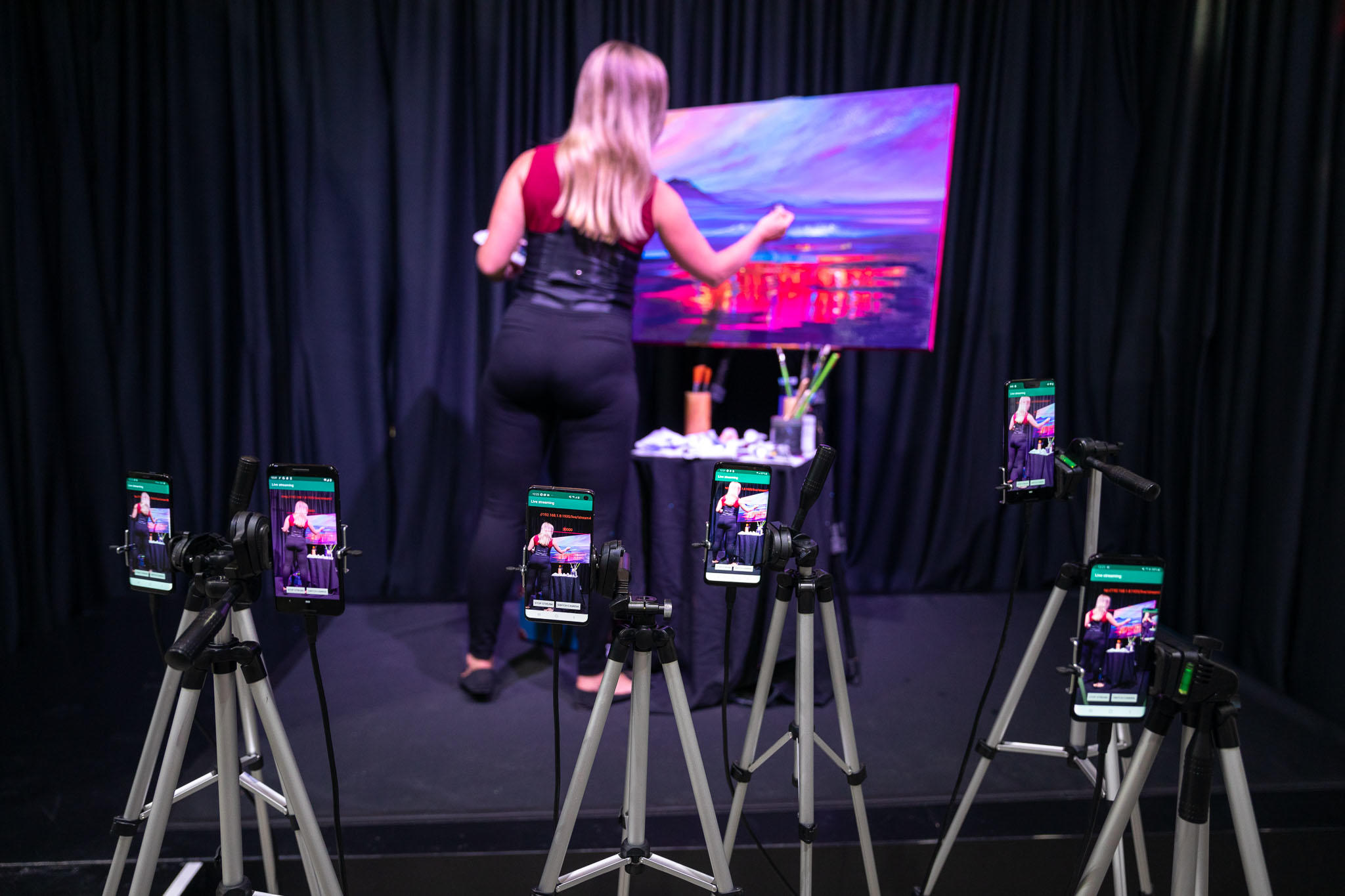 Qualcomm demonstrated coming improvements to Wi-Fi upload speeds by live-streaming a painter with 10 mobile phones.
