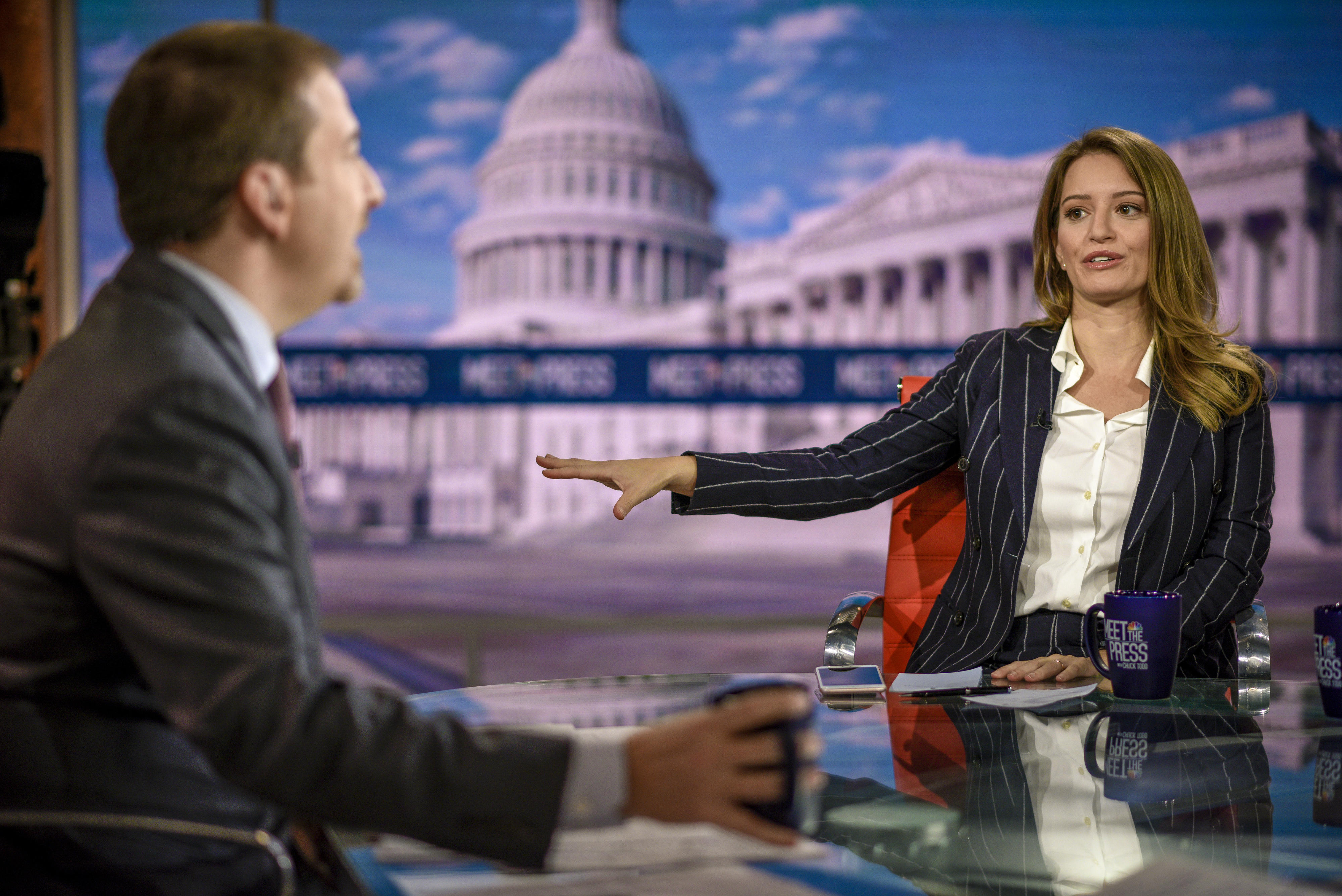 Katy Turn sits at an anchors desk with colleague Chuck Todd in the foreground