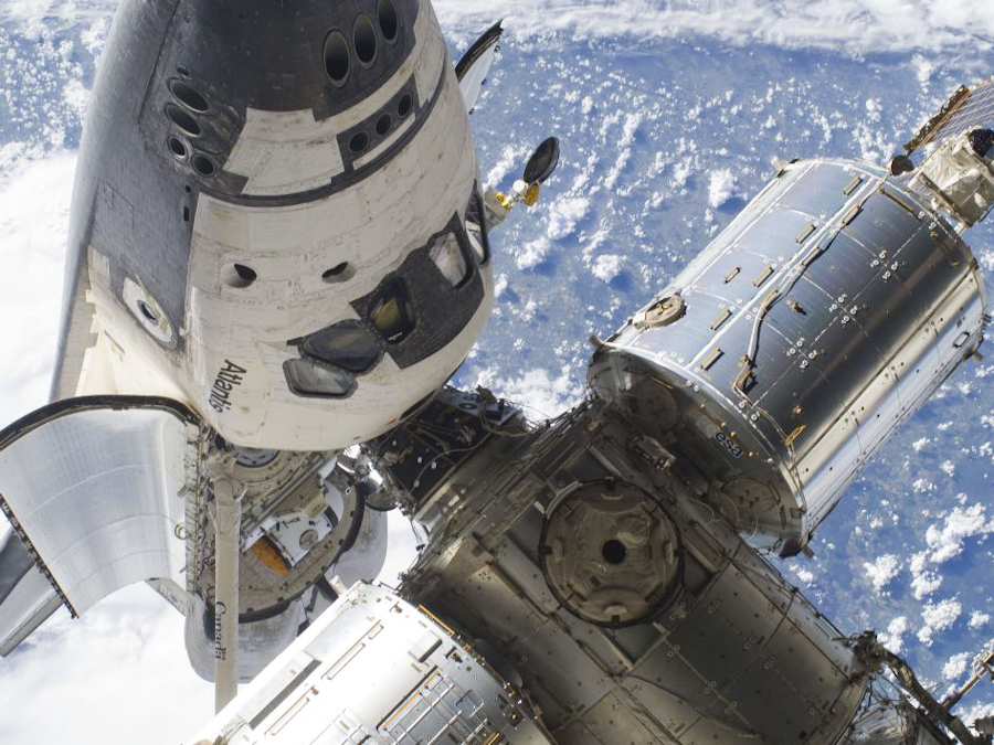With its cabin and open cargo bay visible as it docks with the International Space Station, Atlantis is photographed during the STS-132 mission's first spacewalk on May 18.