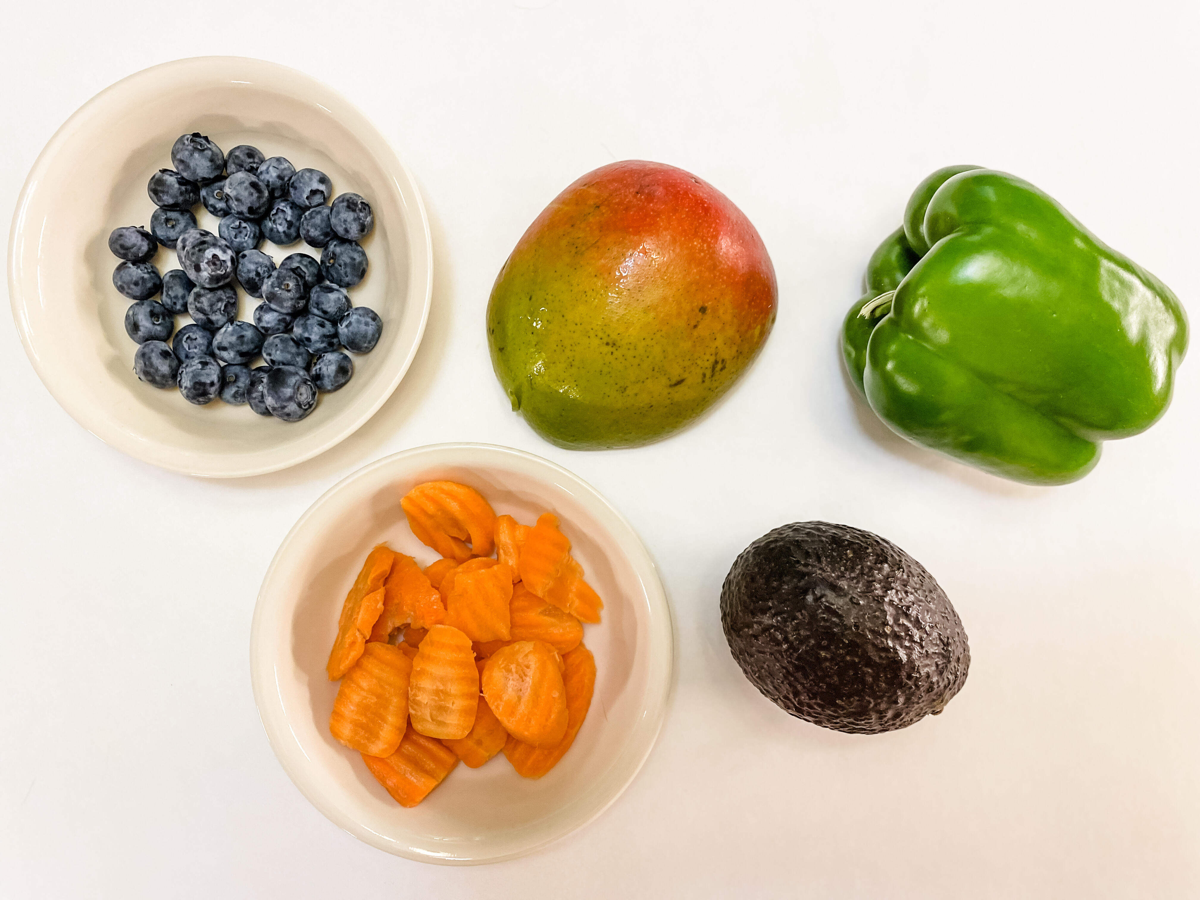 Five servings of produce: half a cup of blueberries, half a mango, a bell pepper, an avocado, half a cup of carrots