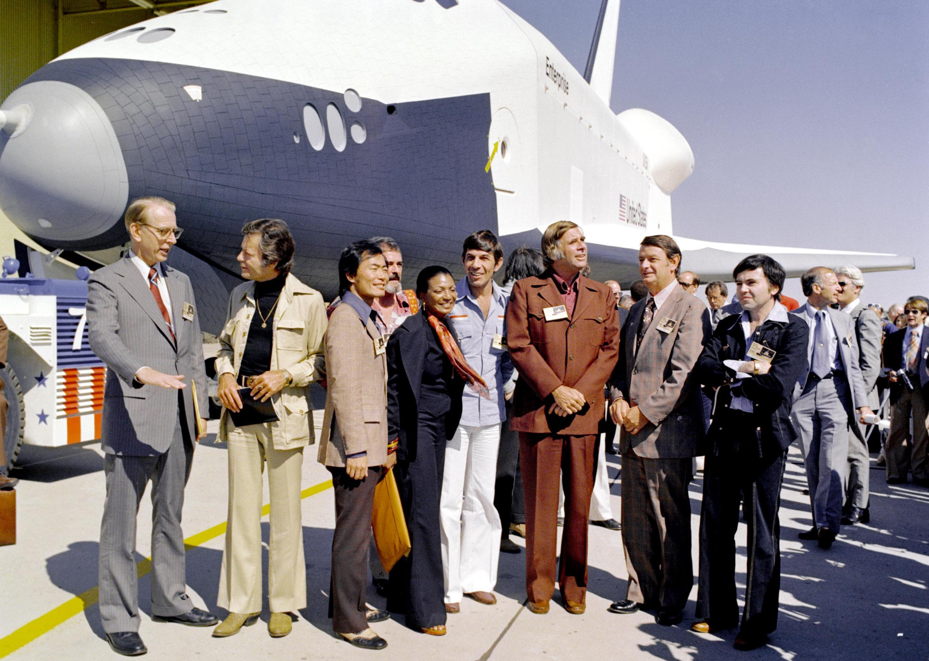 Members of the original Star Trek cast stand in front of the space shuttle Enterprise in 1976. Left to right: James D. Fletcher, NASA administrator; DeForest Kelley (Dr. McCoy); George Takei (Mr. Sulu); Nichelle Nichols (Lt. Uhura); Leonard Nimoy (Mr. Spock); Gene Roddenberry (Star Trek's creator); an unidentified man; and Walter Koenig (Ensign Pavel Chekov). The bearded fellow behind Takei and Nichols appears to be James Doohan (Mr. Scott).