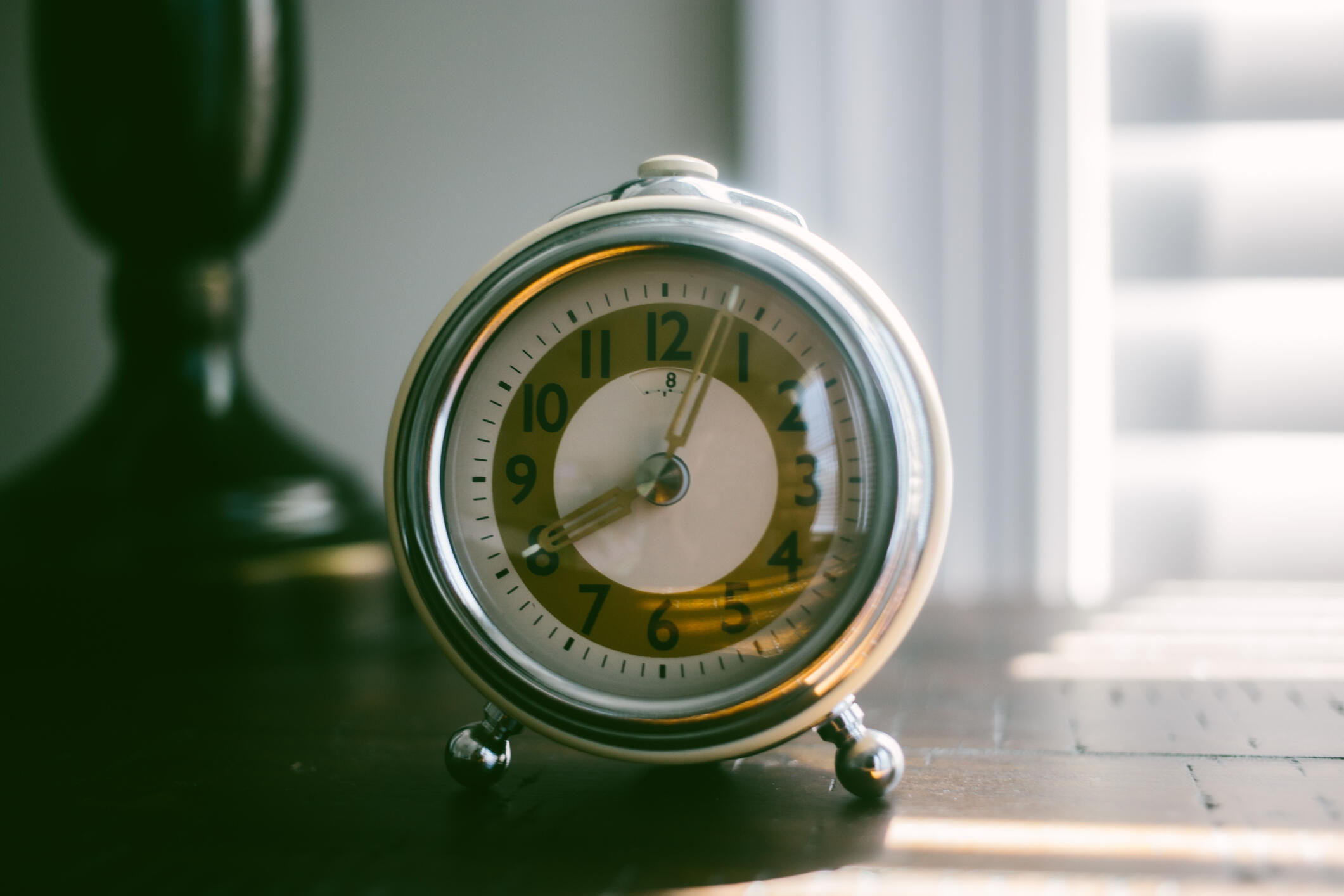a vintage alarm clock on a nightstand