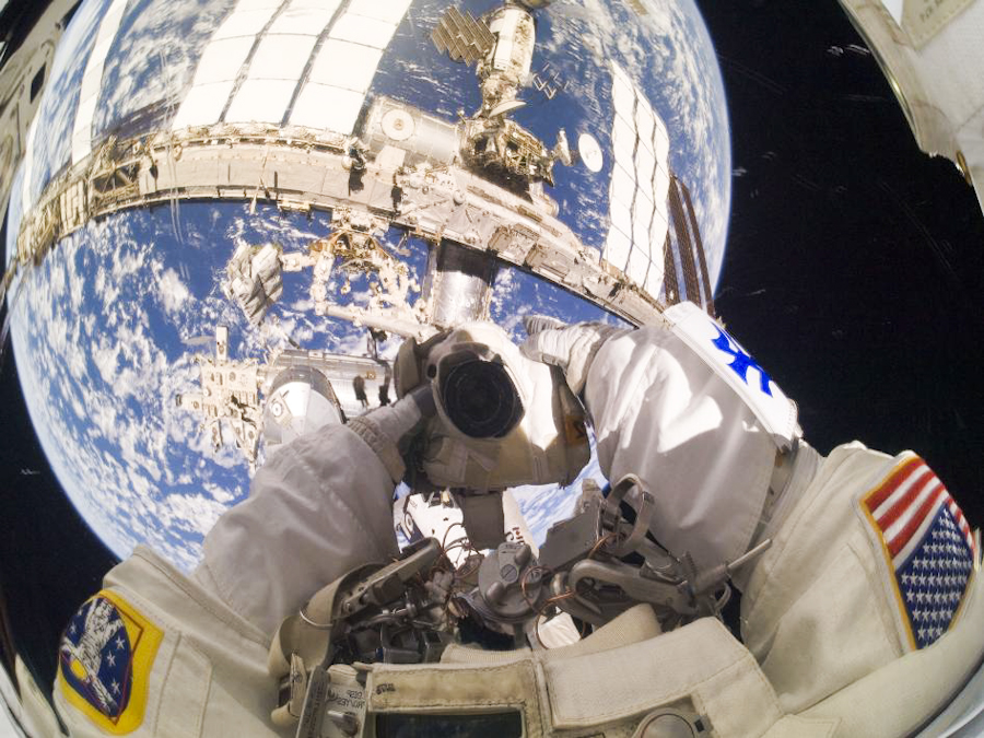 With part of the space station and the blue and white of Earth visible in the reflection of his visor, astronaut Garrett Reisman takes a self portrait during mission STS-132's first spacewalk on May 18.