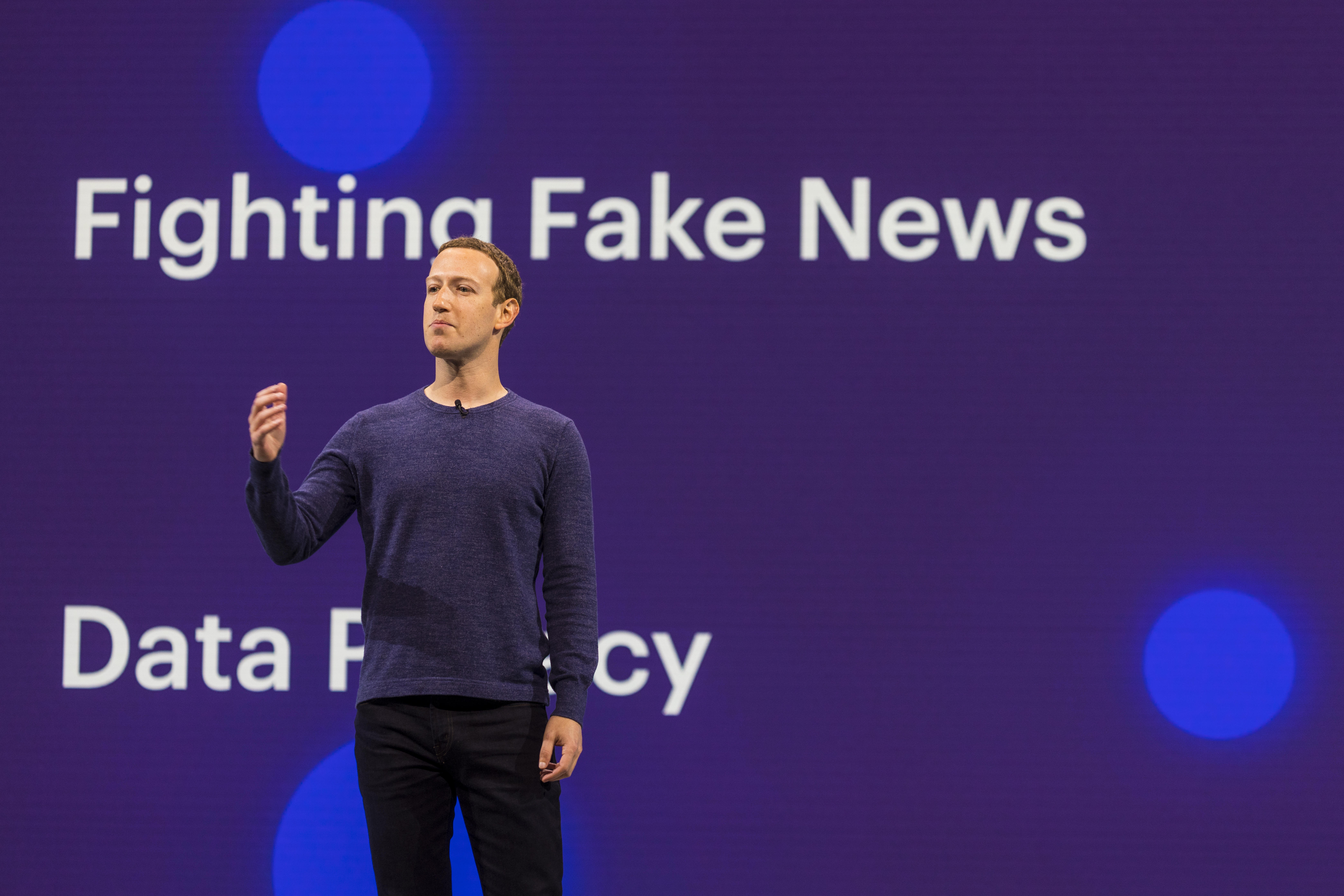 """Facebook CEO Mark Zuckerberg standing in front of a screen that says """"Fighting Fake News."""