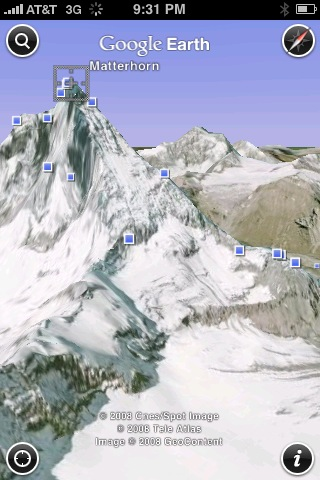 Google Earth for the iPhone can show satellite views of the world in 3D, in this case the Matterhorn, and dots the display with blue squares showing geotagged Panoramio photos.