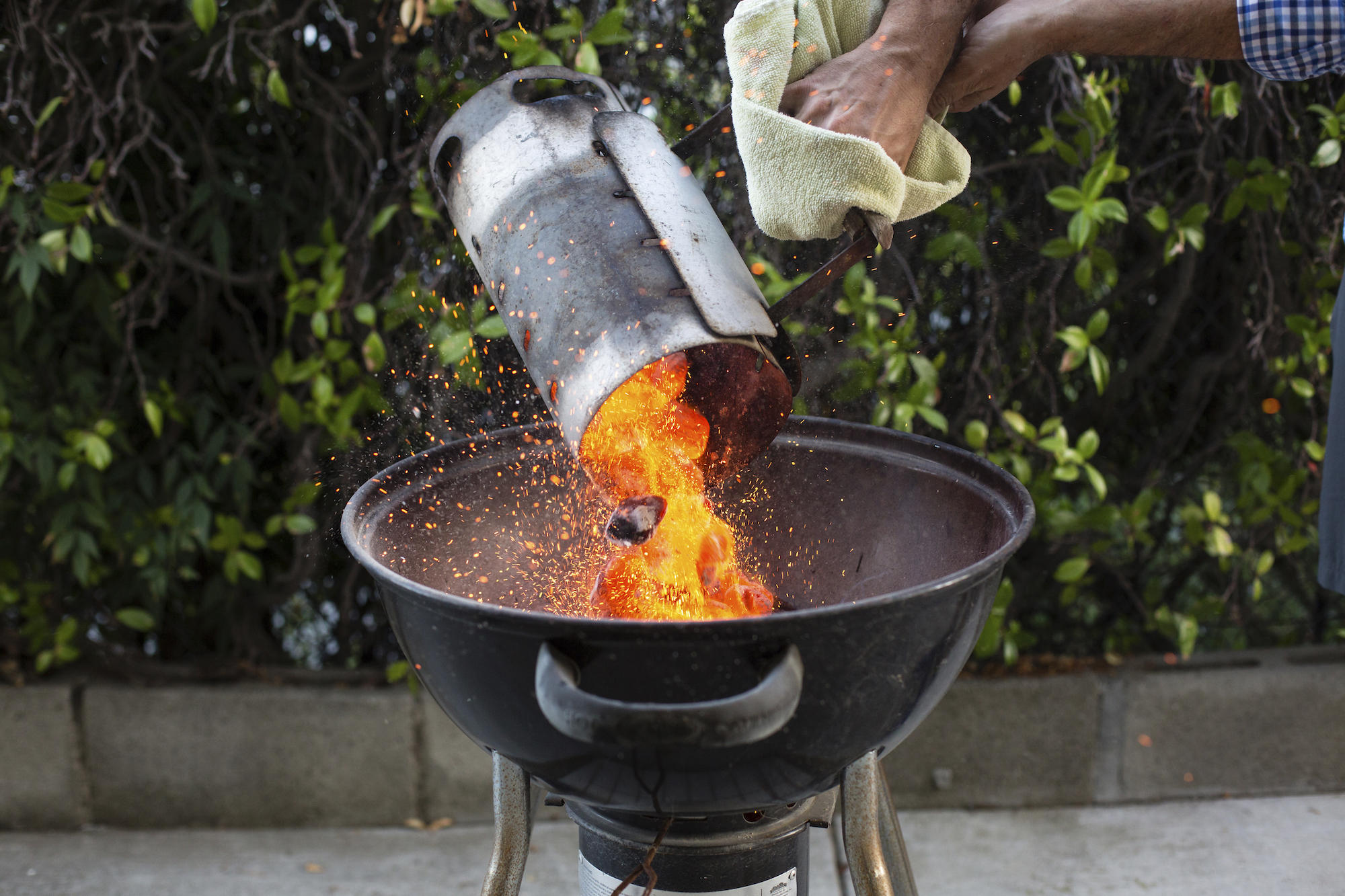 Cropped hands of man putting coals in barbecue at backyard