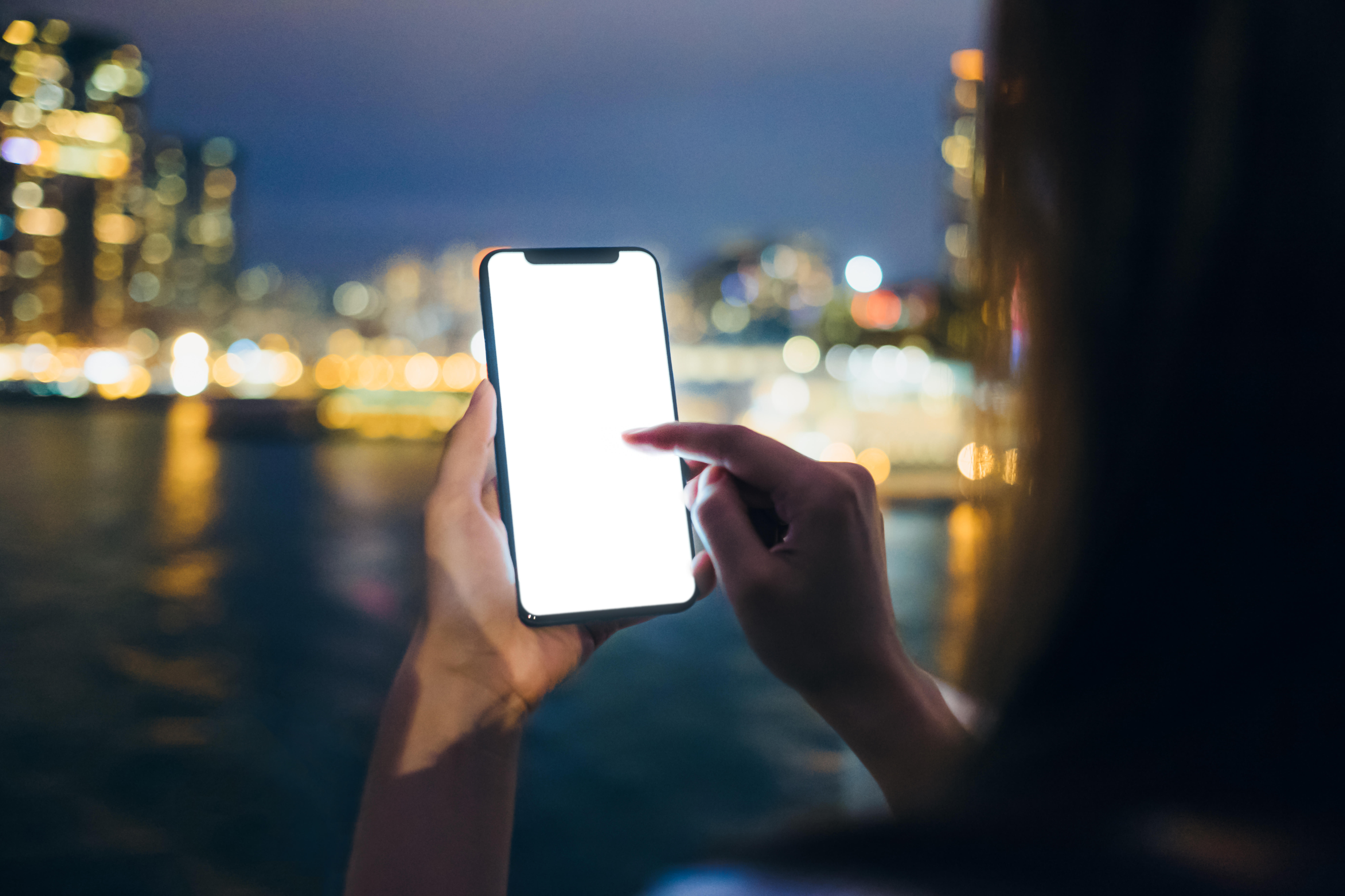 Woman using cell phone by the harbour against illuminated city night view