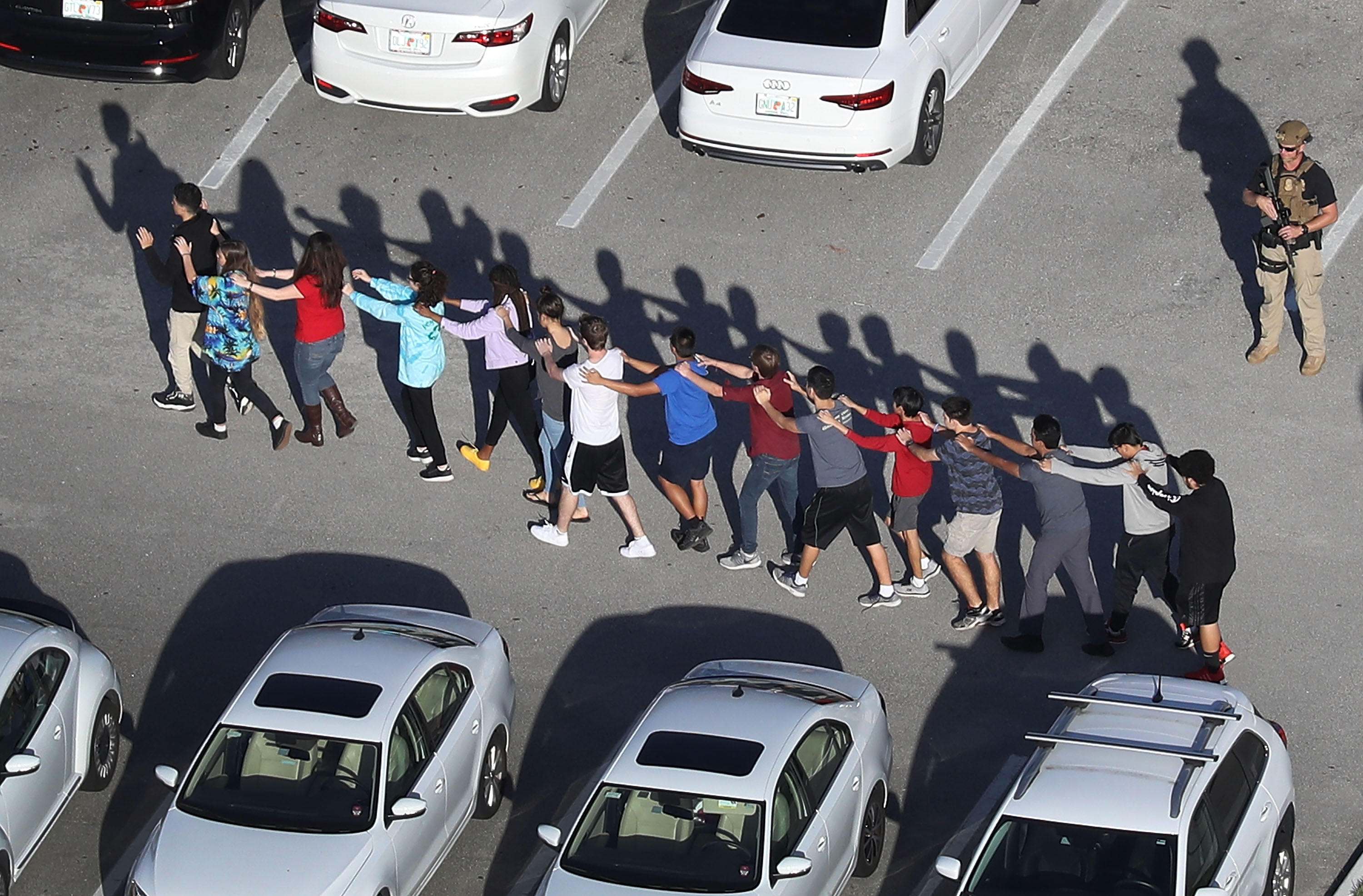 A line of students evacuates the Parkland, Florida, high school where a deadly shooting spree took place.