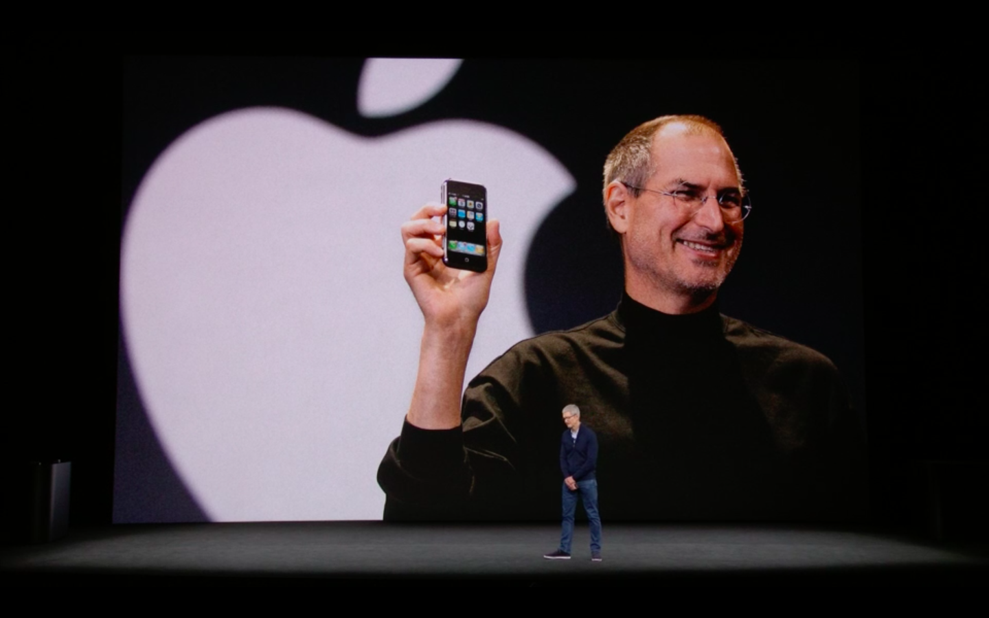 Tim Cook speaking in front of a photo of Steve Jobs at the Apple event on Tuesday.