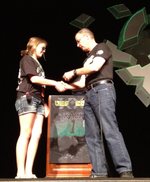 Pre-teen hacker CyFi gets congratulated by Gen. Keith Alexander during a Defcon session for winning a Zero-Day contest as part of Defcon Kids.