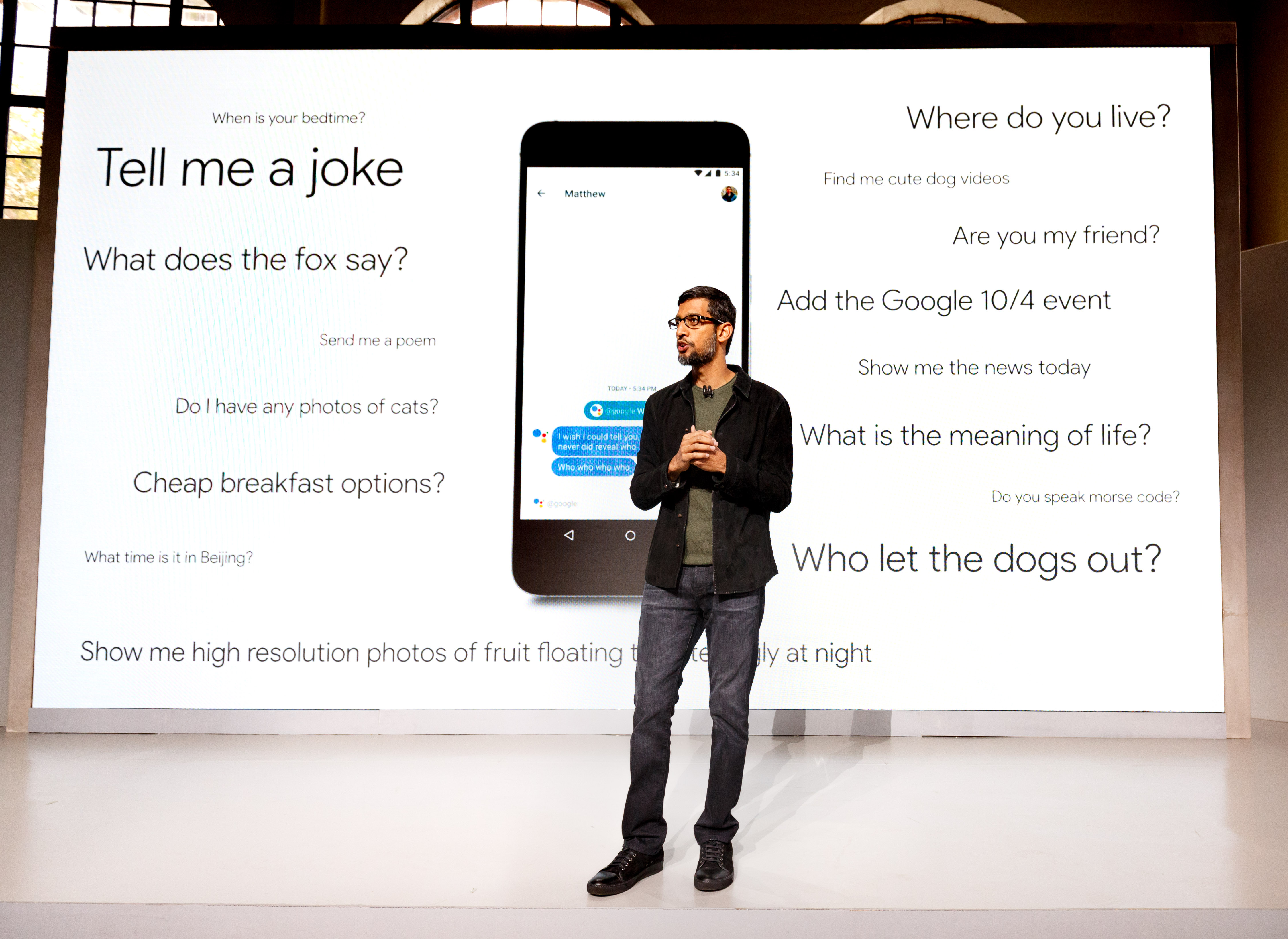 Google CEO Sundar Pichai stands before queries you can ask Google Assistant.