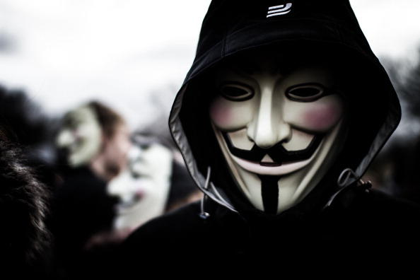 A person wears a Guy Fawkes mask which today is a trademark and symbol for the online hacktivist group Anonymous. 2012.