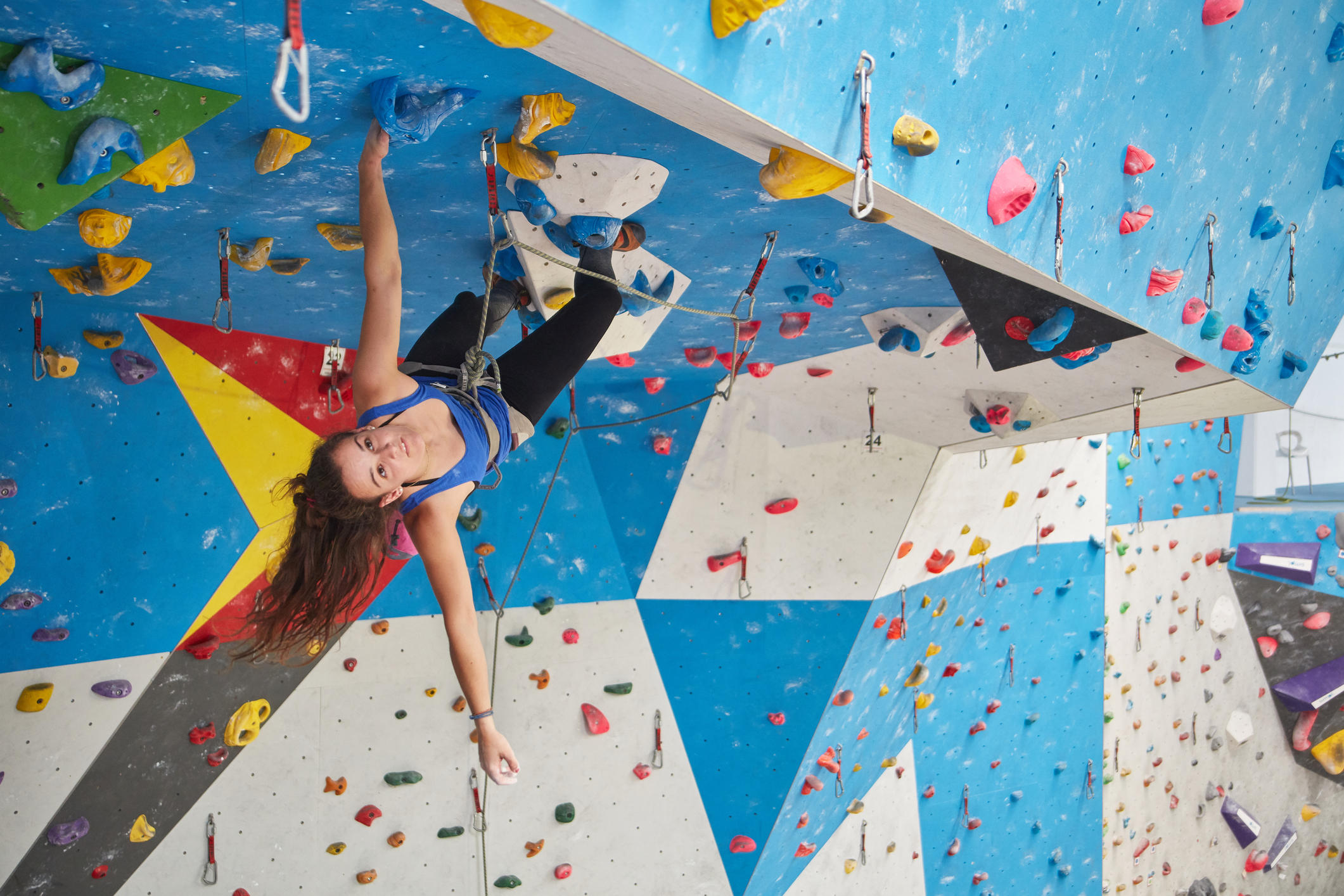 Young woman climbing wall in gym