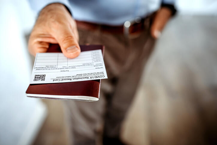 Man holding vaccine card and passport