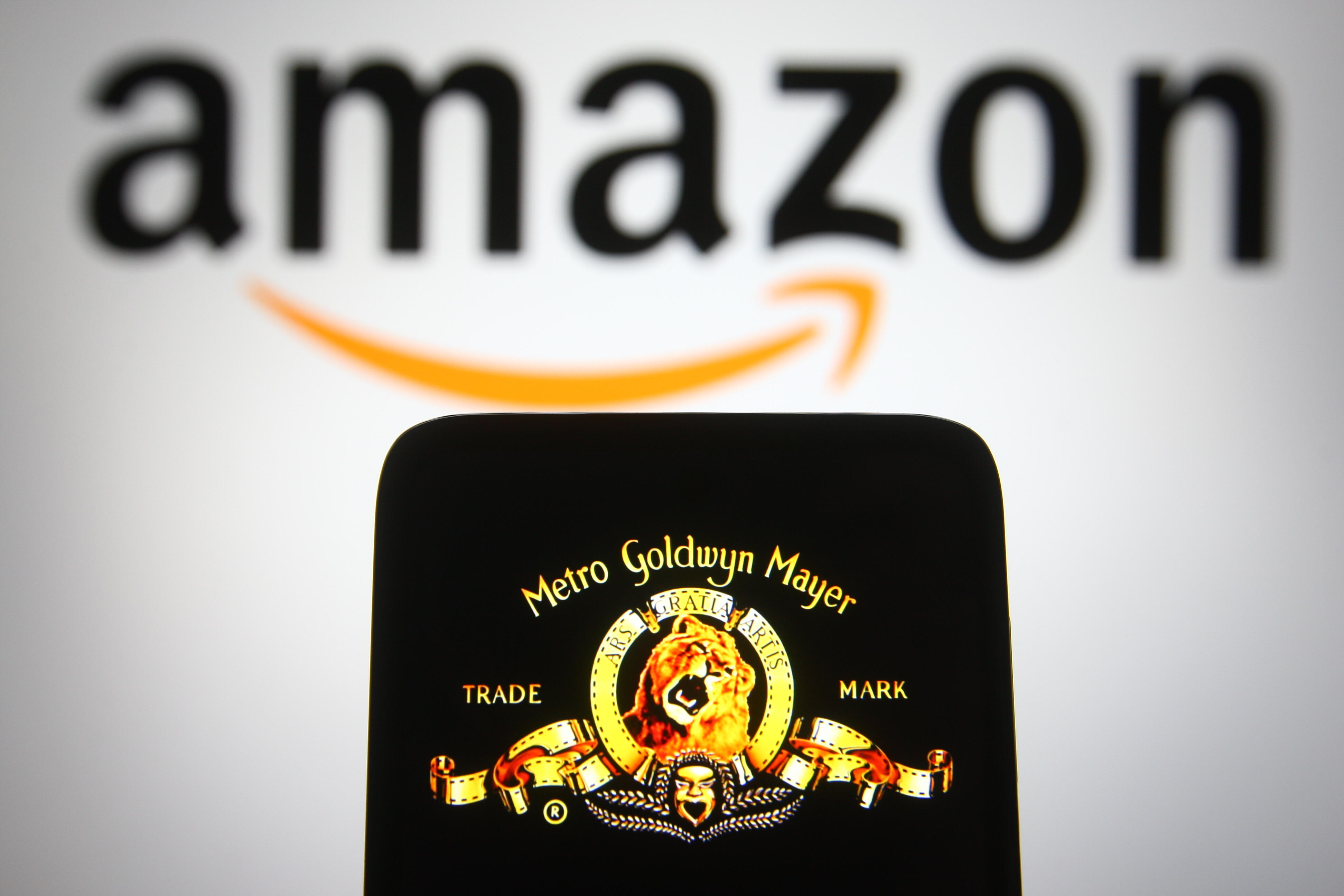 A phone displays the MGM lion logo. Behind the phone is a larger, blurred out Amazon sign.