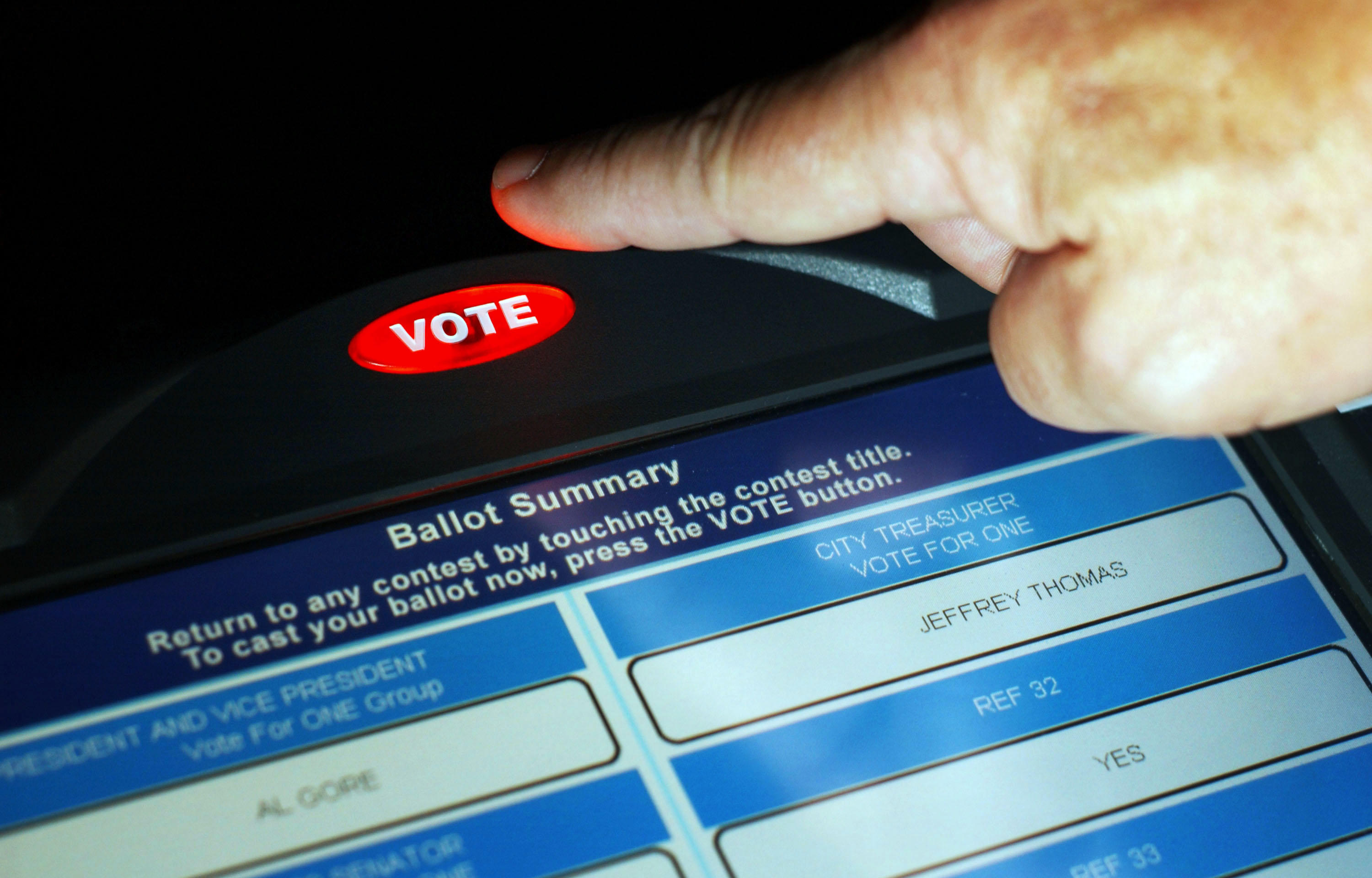 """Close-up of a computerized screen displaying a ballot, and a hand reaching to press a red touch-screen button that says, """"Vote."""""""