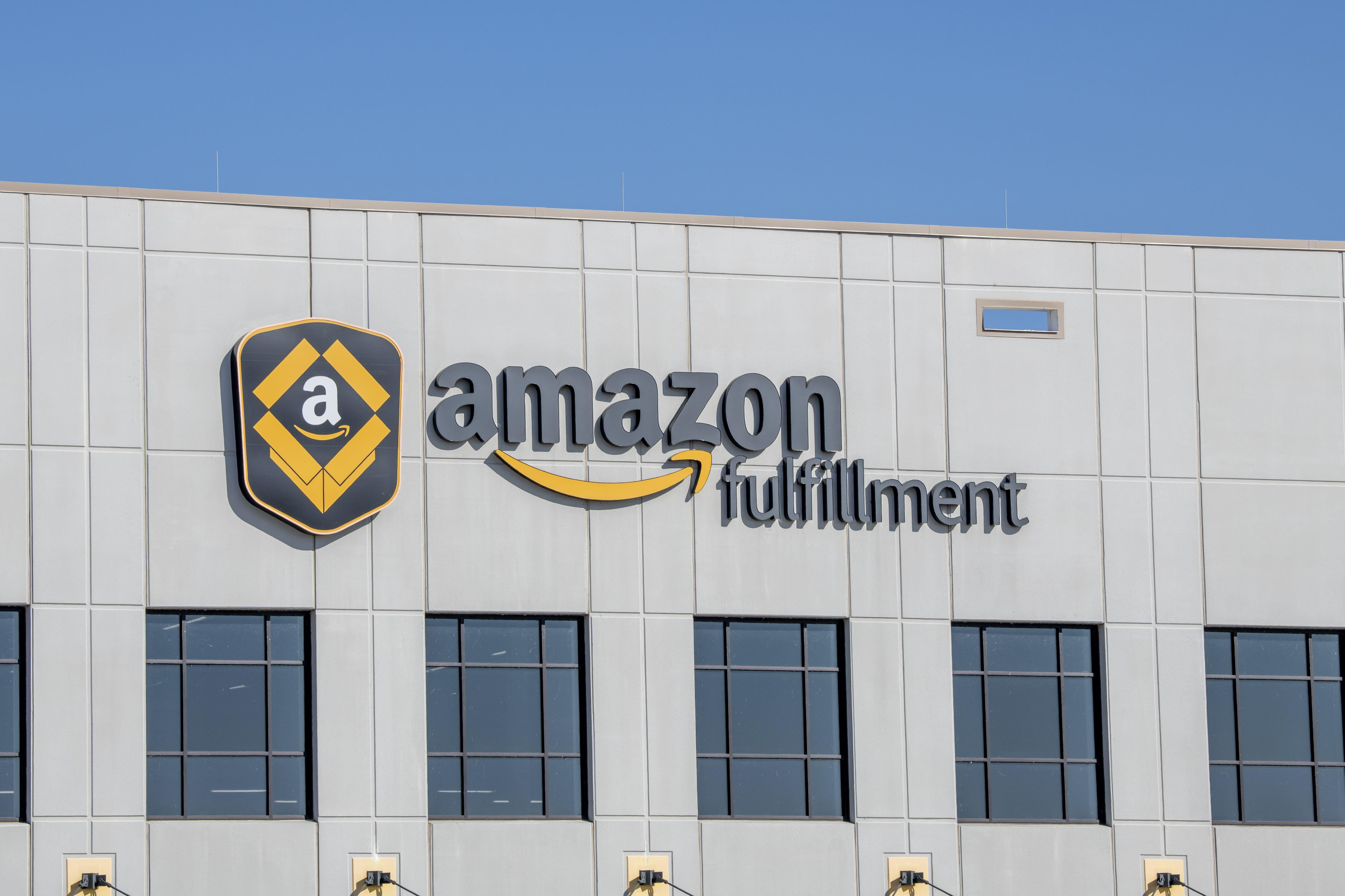 """The outside of a warehouse with a sign saying """"Amazon fulfillment."""""""